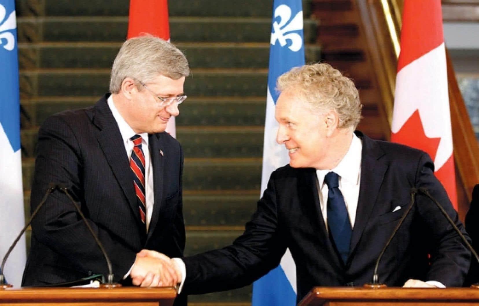 Une poignée de main longtemps attendue entre un premier ministre fédéral et son homologue québécois: le Québec réclame la compensation pour l'harmonisation des taxes de vente depuis 1992.<br />