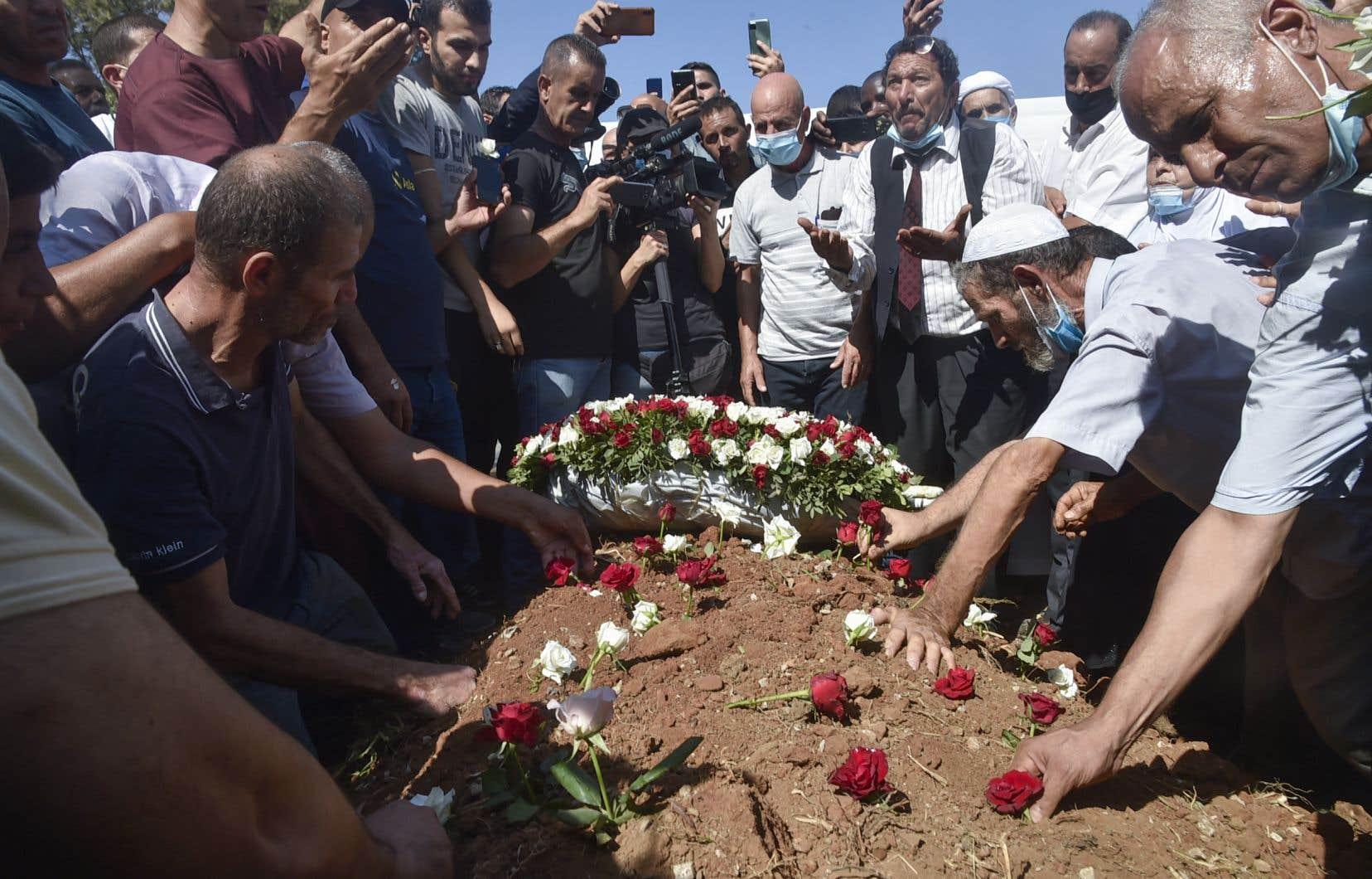 Des Algériens déposent des roses sur la tombe de l'ancien président Abdelaziz Bouteflika lors de ses funérailles au cimetière El-Alia d'Alger.
