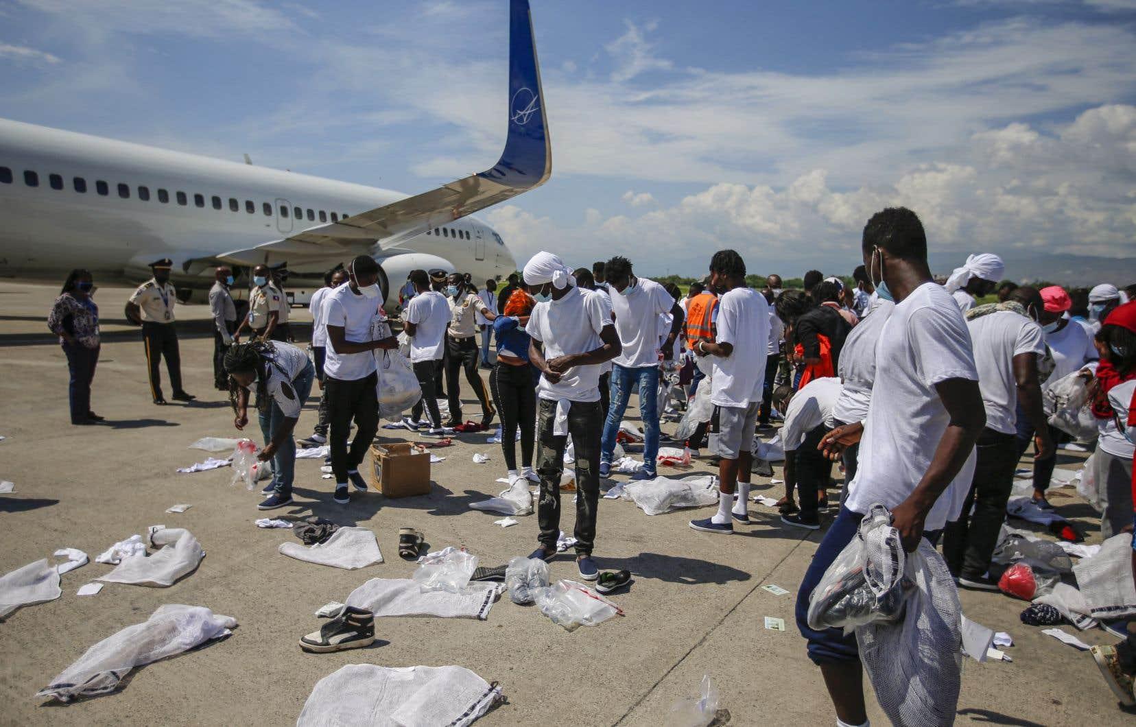 Des Haïtiens expulsés des États-Unis récupèrent leurs biens éparpillés sur le tarmac de l'aéroport Toussaint Louverture à Port-au-Prince, Haïti, le 21 septembre 2021.