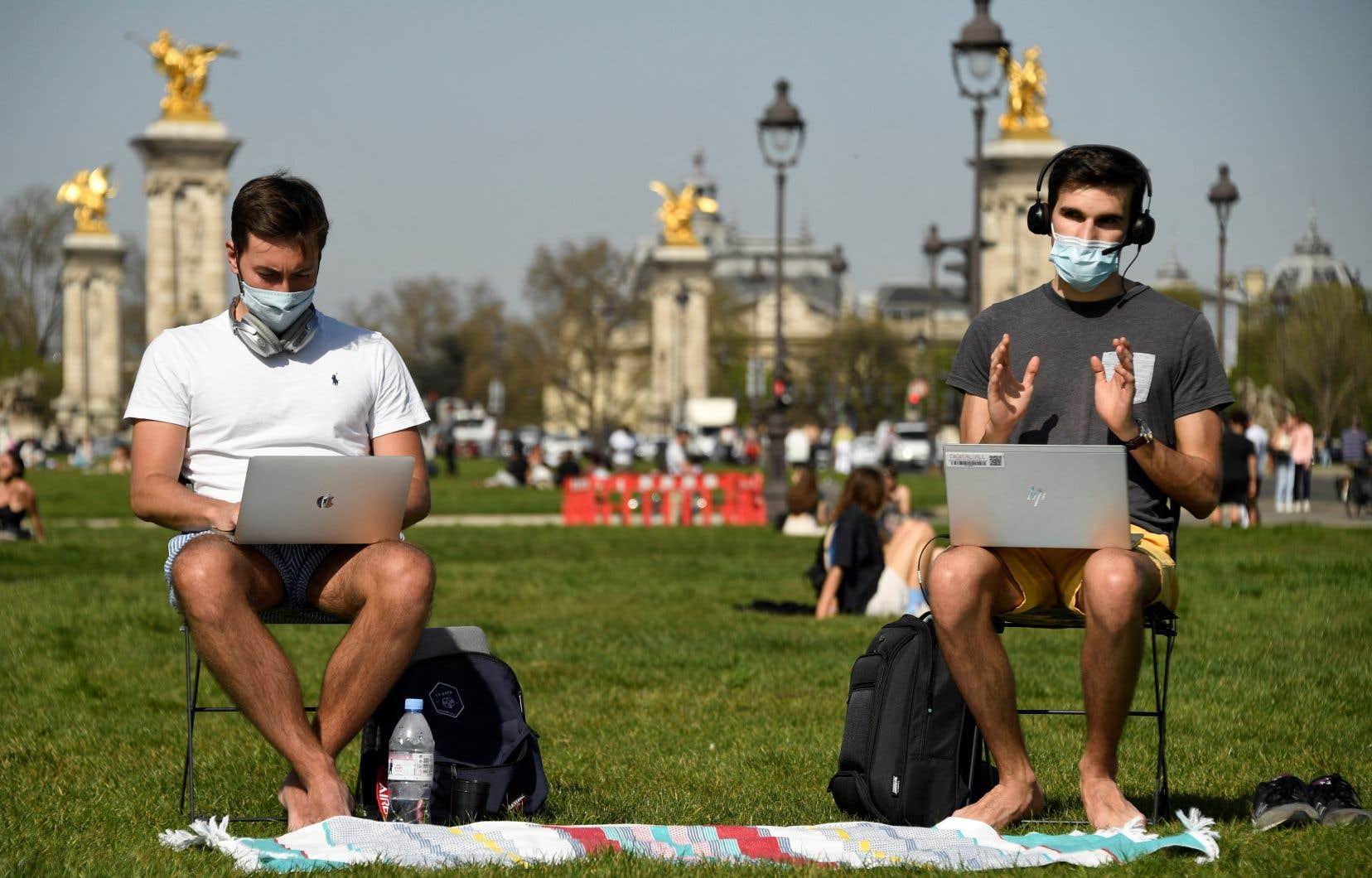 Deux hommes travaillant, les pieds dans l'herbe, devant l'hôtel des Invalides, à Paris