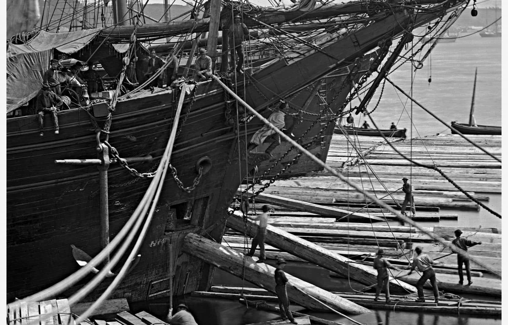 Des hommes chargeant du bois équarri à bord d'un navire à Québec, en 1872.