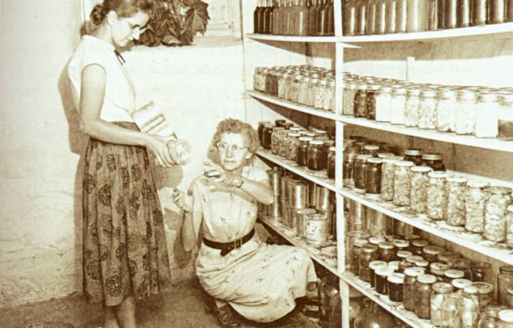 Un garde-manger rempli de pots de confiture vari&eacute;es. Mme Phiippe P&eacute;pin et sa fille Denise, Warwick, Arthabasca, 1957. <br />