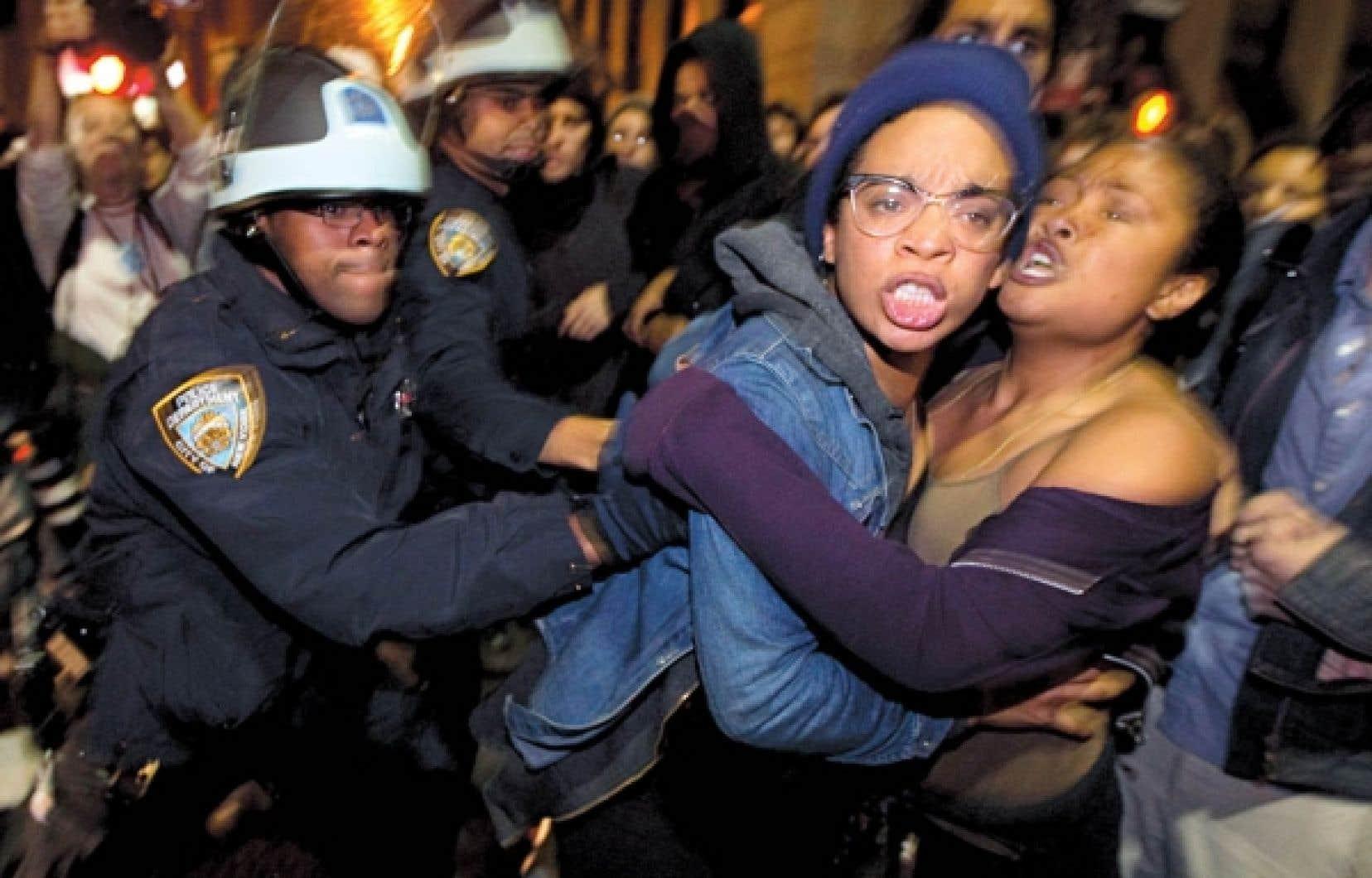 Des policiers new-yorkais bousculent des membres d'Occupy Wall Street, au cours du raid-surprise qui s'est déroulé hier, au beau milieu de la nuit.<br />