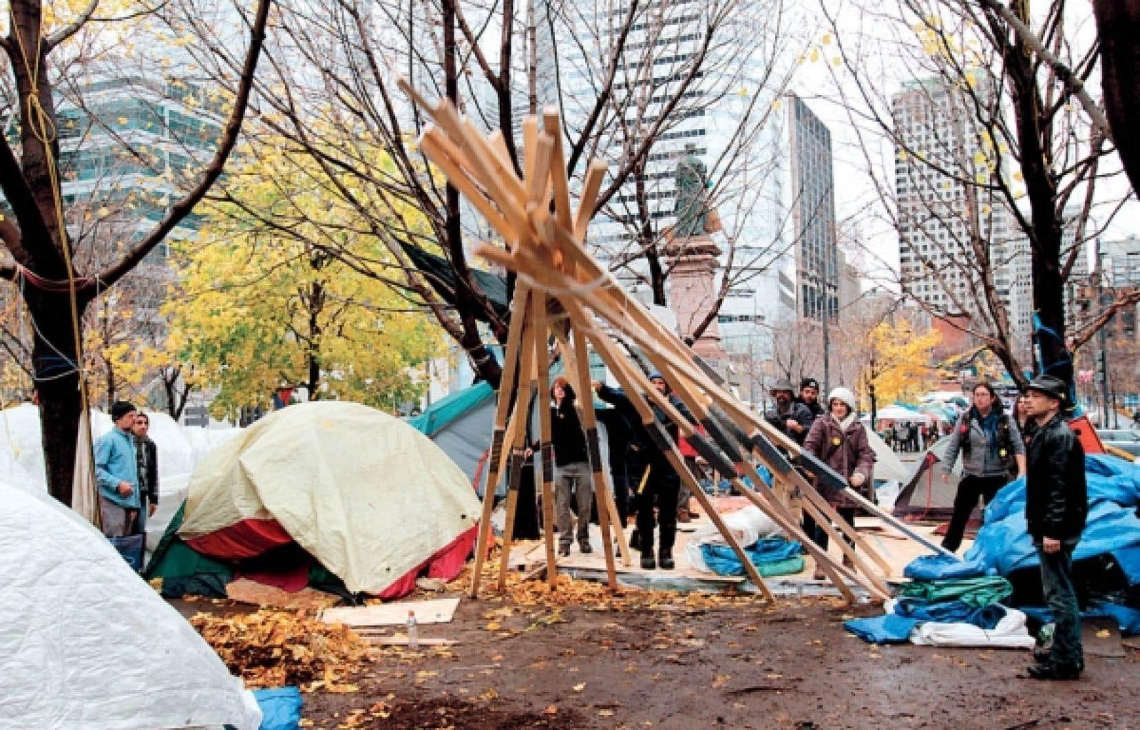 Les indignés montréalais ont poursuivi hier la démolition d'abris illégaux au profit de tentes militaires censés les aider à passer l'hiver au square Victoria.<br />