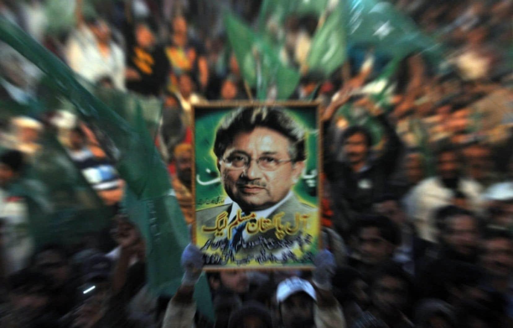 Un militant tient un portrait de Pervez Moucharraf durant une réunion publique qui s'est déroulée hier à Karachi. Moucharraf a déclaré hier qu'il reviendrait à domicile après plus de trois ans d'exil.<br />