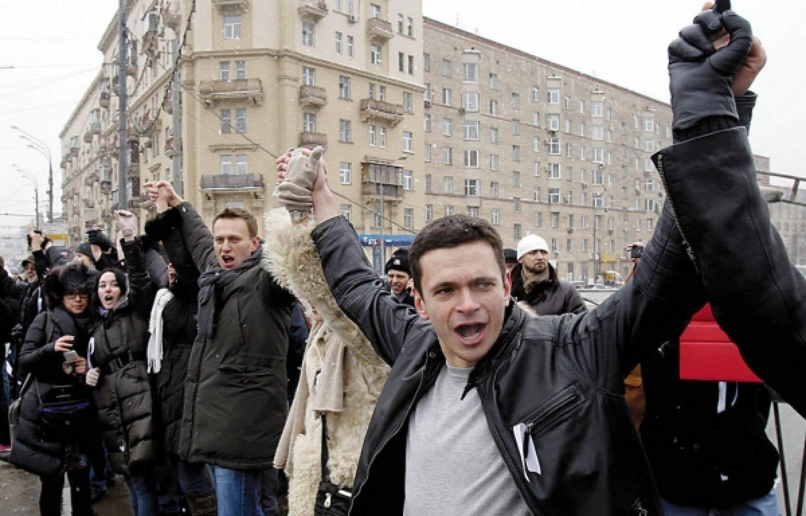 L'activiste et blogueur Alexei Navalny (au centre, foulard gris) participe à une chaîne humaine formée autour du centre de Moscou, dimanche dernier, par des centaines d'opposants au retour de Vladimir Poutine au poste de président.<br />