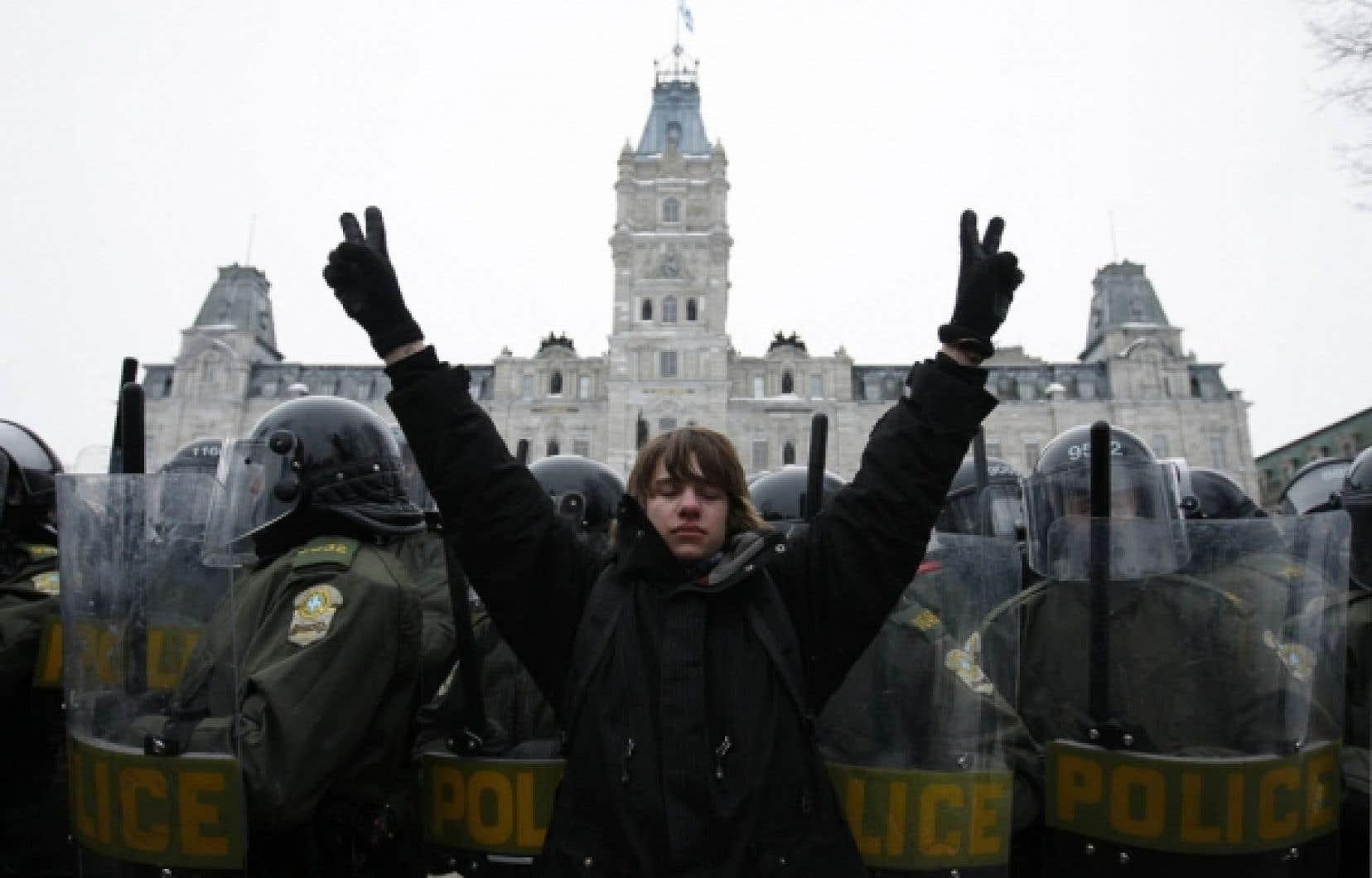Un étudiant brandit le signe de la victoire devant un cordon de policiers de l'escouade antiémeute de la SQ déployé devant le parlement à Québec.<br />