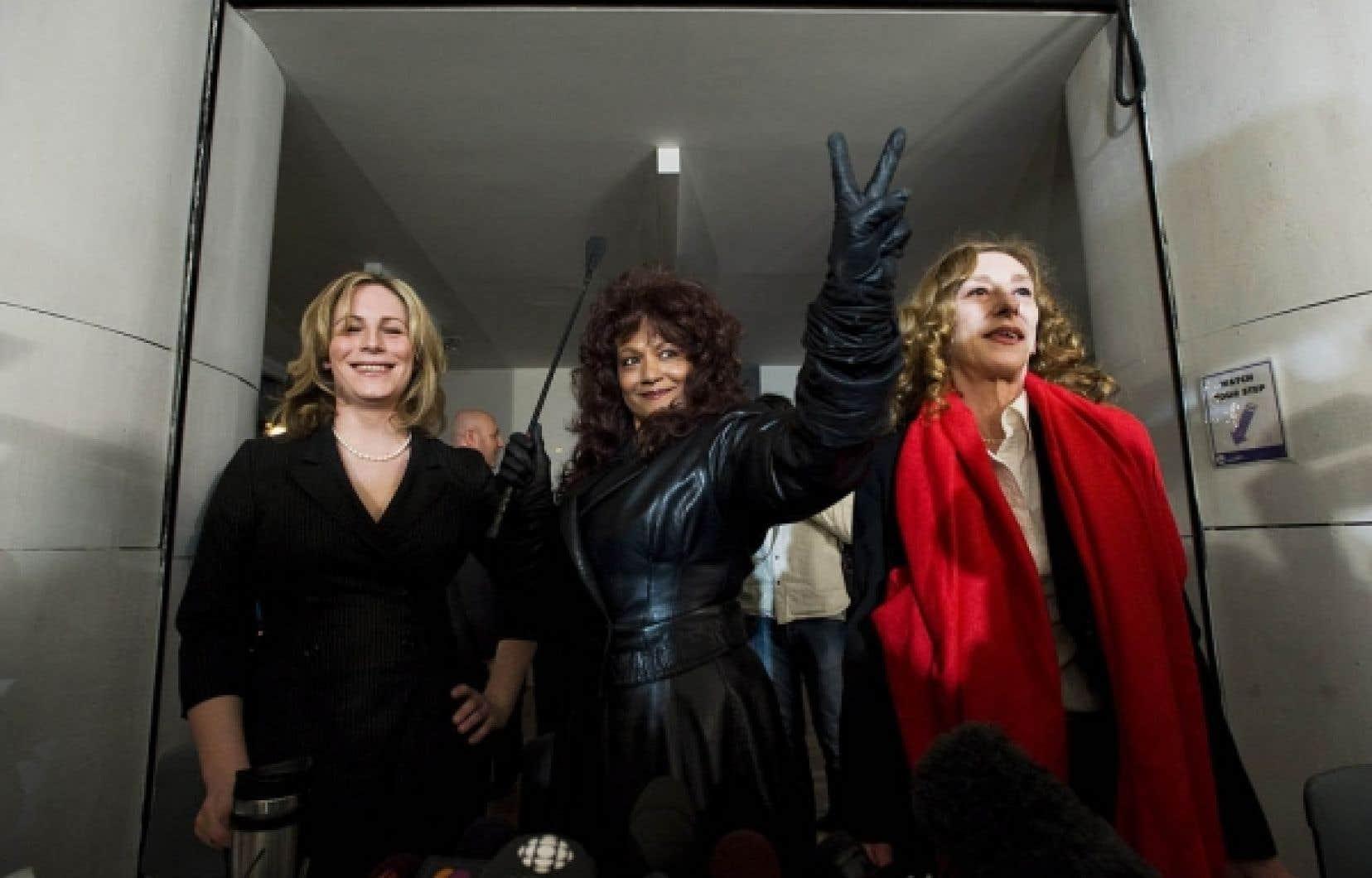 Terri Jean Bedford, entourée de Nikki Thomas (à gauche) et de Valerie Scott, fait le signe de la victoire après l'annonce, hier, de la légalisation des maisons de débauche par la Cour d'appel de l'Ontario.