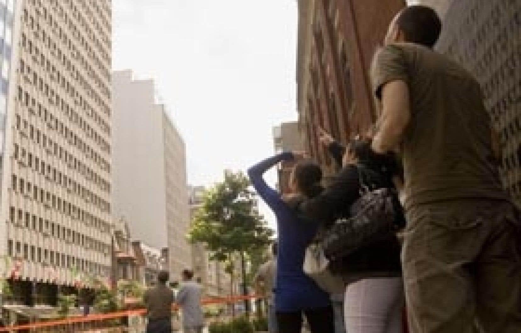 Des passants regardent vers le 17e étage de l'hôtel Marriott pour voir d'où la dalle de béton s'est détachée.