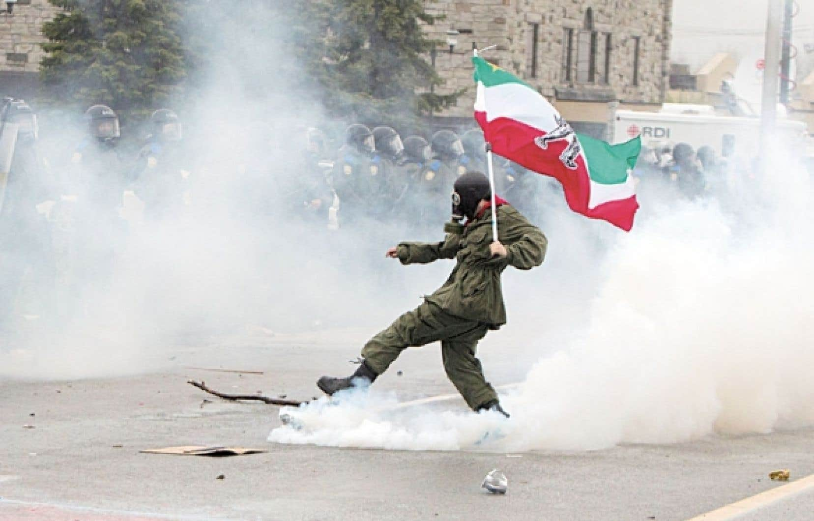 La crise a pris des proportions qui n'ont plus rien à voir avec les revendications de départ des étudiants. Ici, un manifestant muni d'un drapeau des Patriotes défiant des policiers, à Victoriaville.