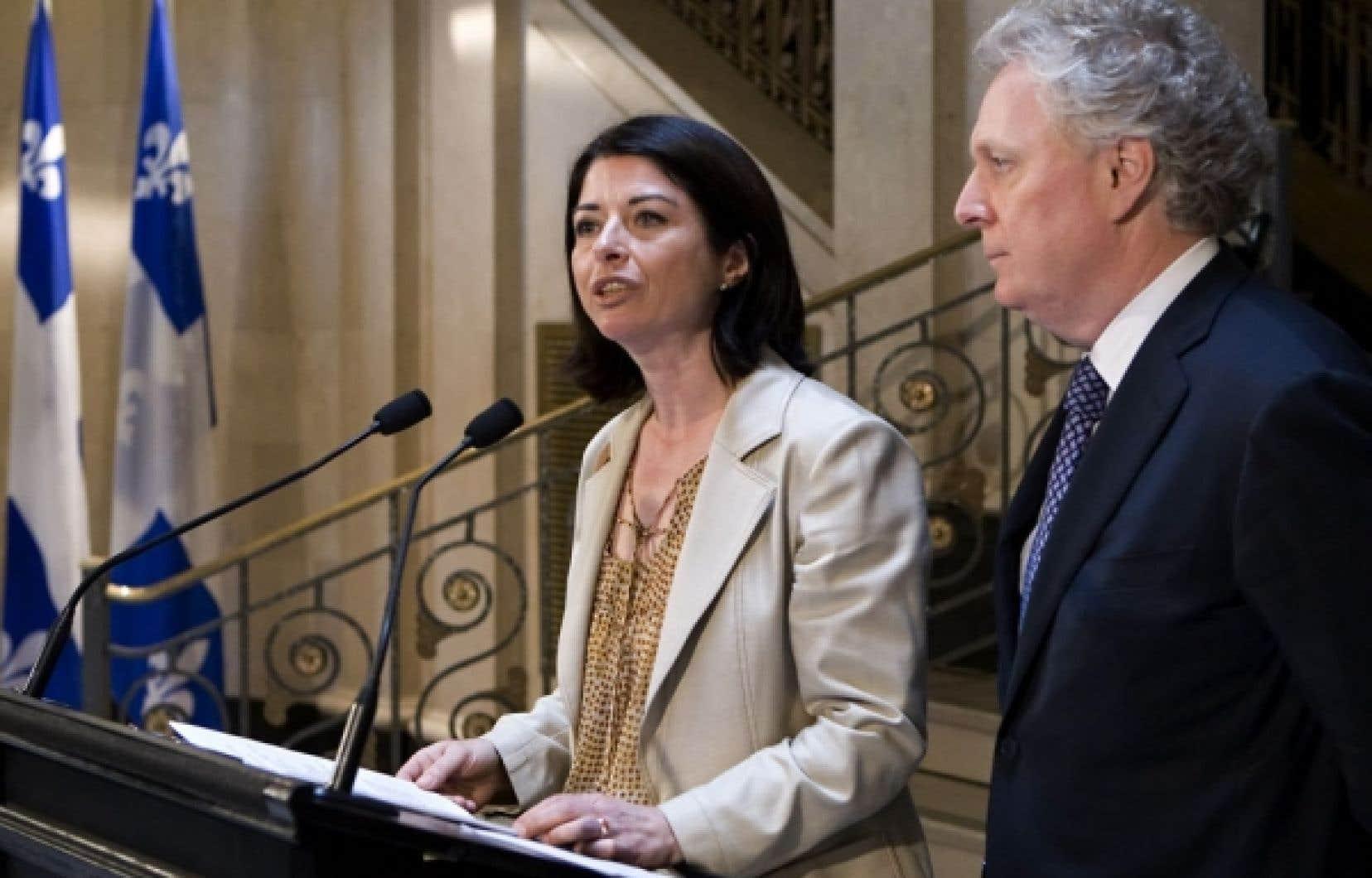 La ministre de l'Éducation, Line Beauchamp, annonçant sa démission, hier, à Québec, aux côtés du premier ministre Jean Charest. Mme Beauchamp a estimé ne plus faire « partie de la solution » dans la crise étudiante.