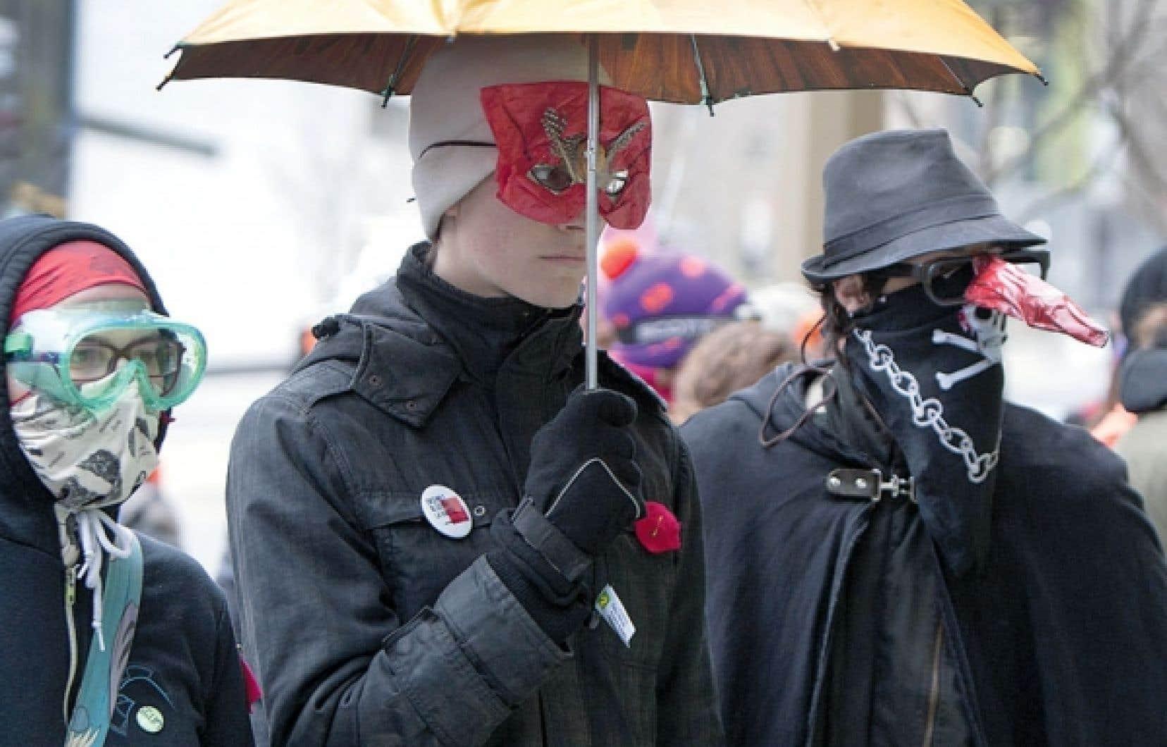 Des étudiants masqués manifestent contre la hausse des droits de scolarité.