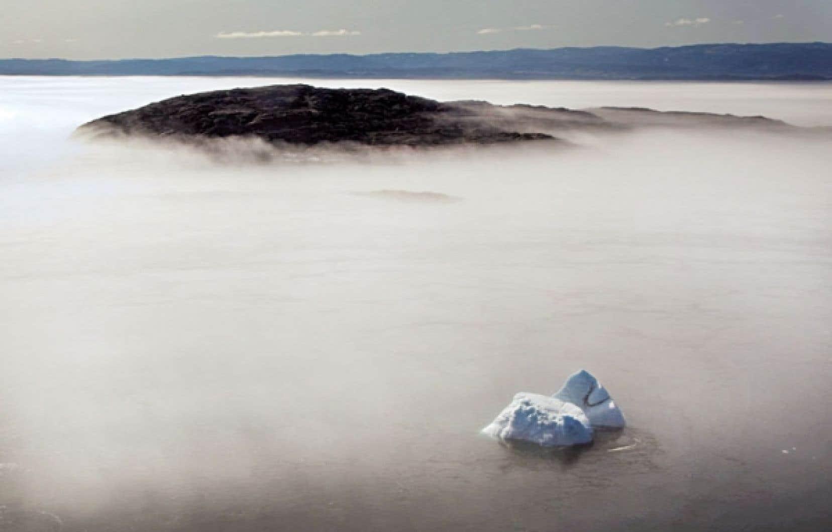 Un iceberg émerge du brouillard matinal à Frobisher Bay, dans l'Arctique canadien. L'Arctique, de plus en plus accessible en raison de la fonte des glaces, suscite la convoitise des pétrolières.