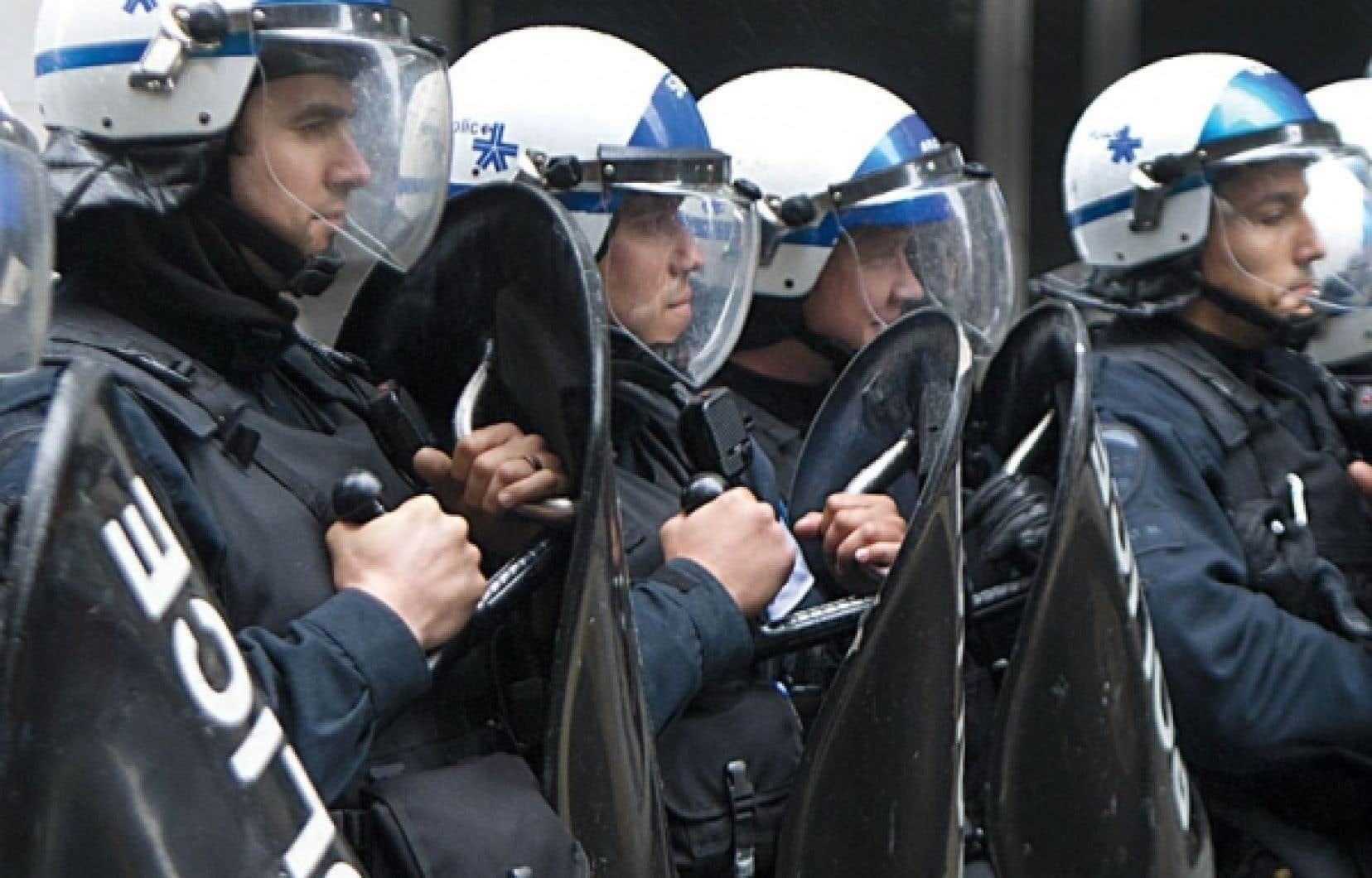 Des policiers du Service de police de la Ville de Montréal s'apprêtent à intervenir lors d'une manifestation.