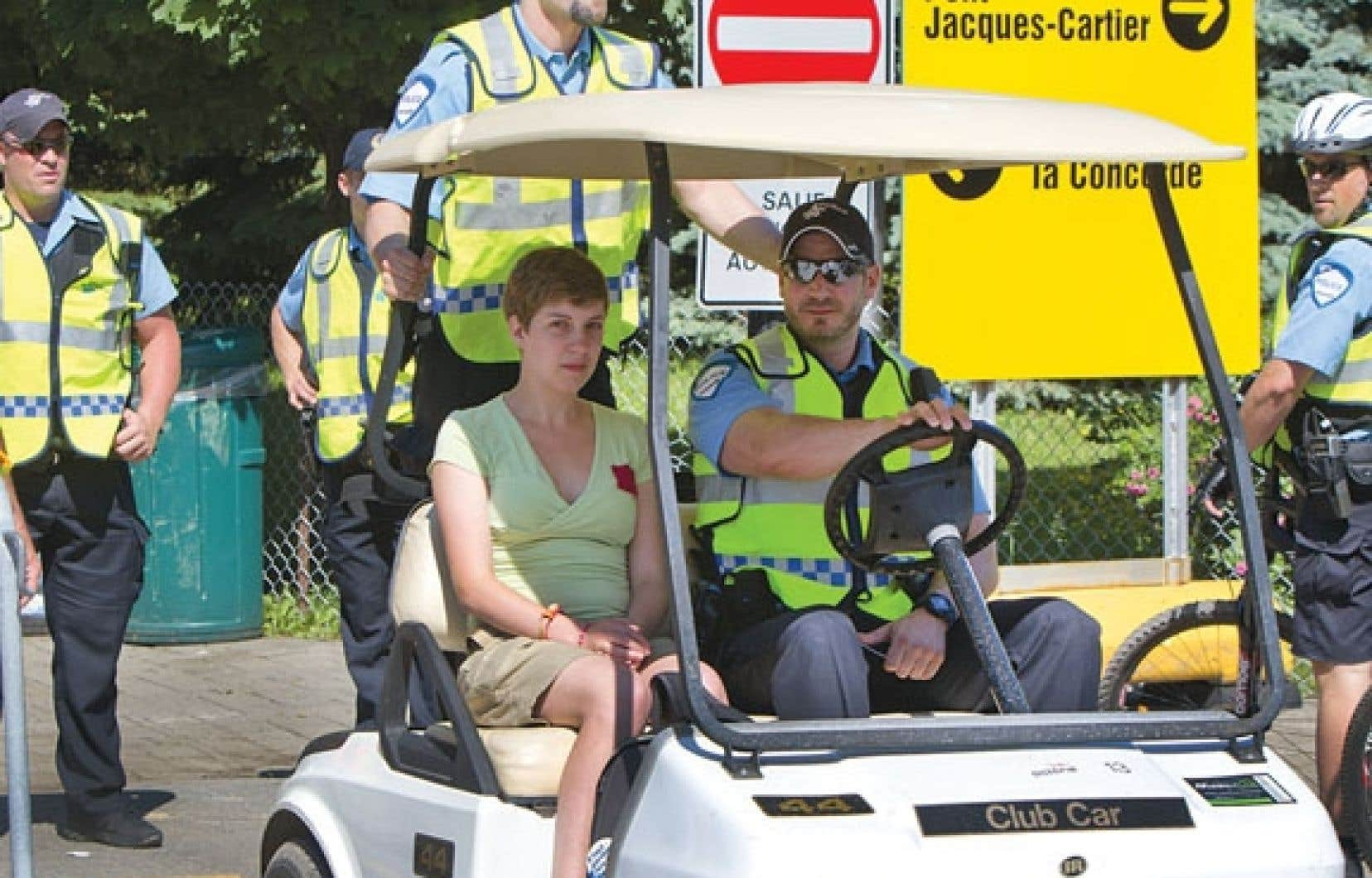 Une jeune femme portant le carré rouge est escortée par les policiers.