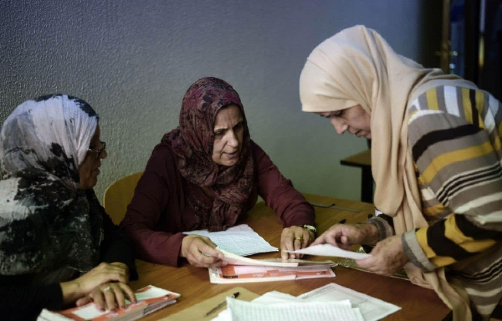 Des employées d'un bureau de scrutin de Tripoli vérifiaient la liste électorale, hier, à la veille des élections.