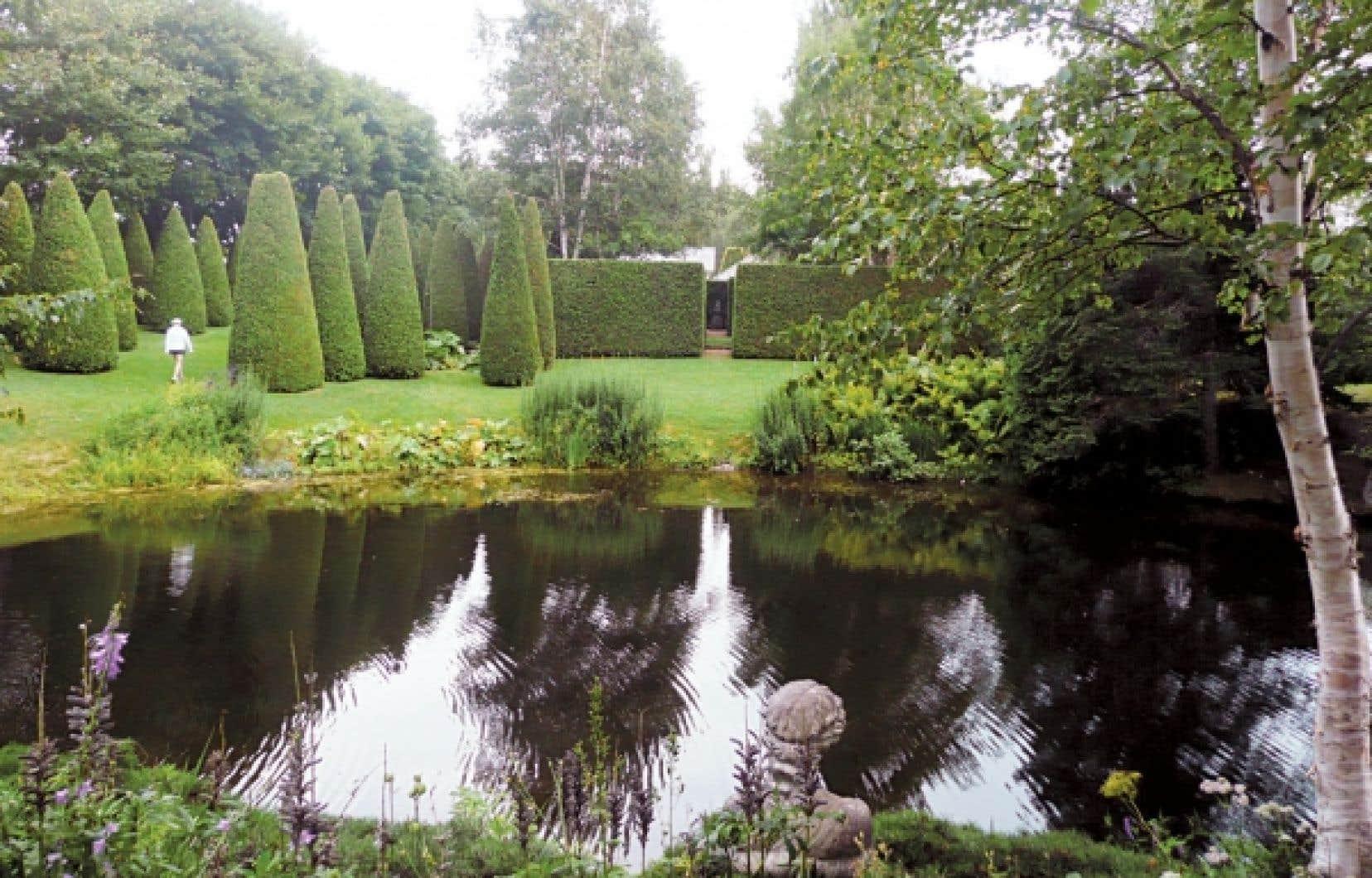 <div> Les jardins de Quatre-Vents, dans Charlevoix, font partie des grands jardins privés de l'Amérique du Nord. Voici l'impeccable et impressionnante allée des thuyas et, à l'avant-plan, le lac des Libellules.</div>