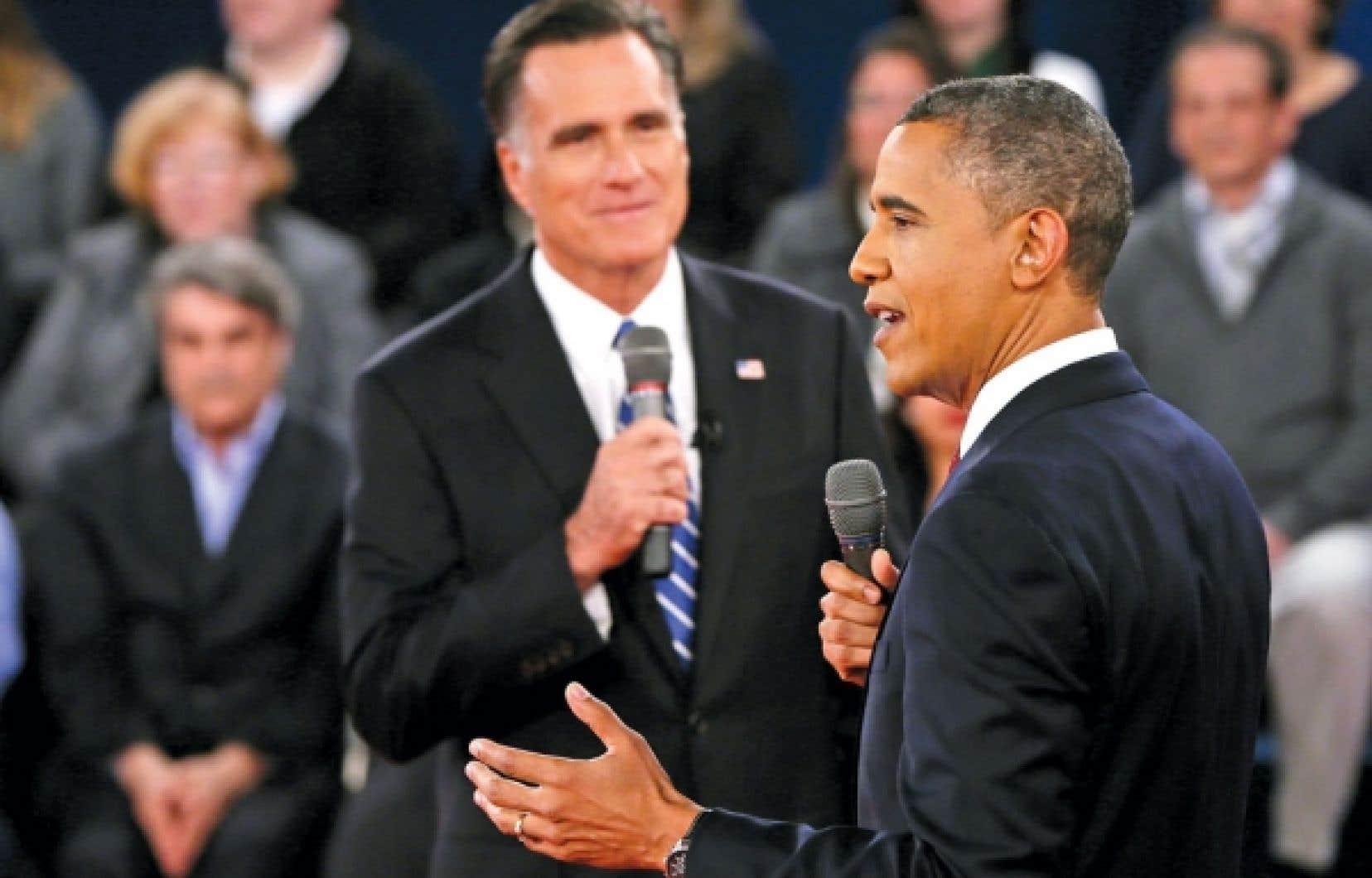 Le président des États-Unis, Barack Obama, répondant à une question venant de l'auditoire sous l'œil du républicain Mitt Romney, mardi, lors du deuxième débat des candidats à la présidence tenu à l'Université Hofstra, à Long Island, dans l'État de New York. M. Obama s'est montré pugnace, attaquant son rival dès le début.