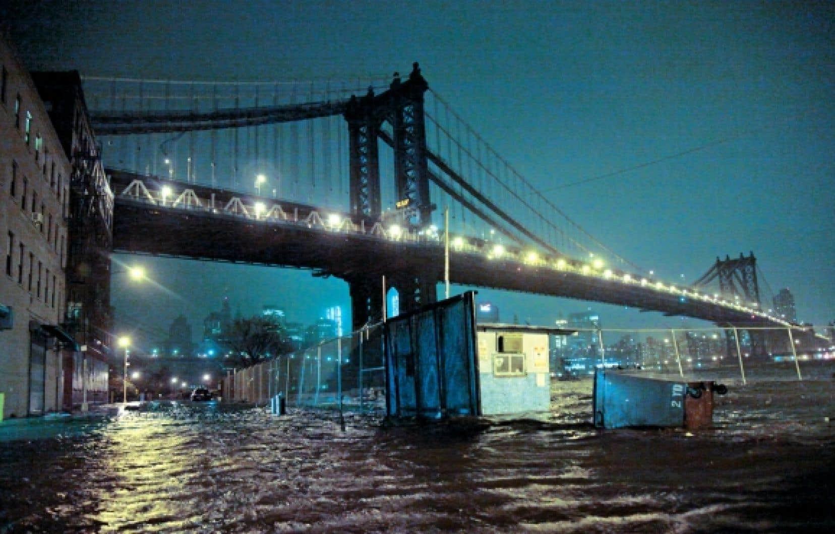 <div> L'eau inondait les rues sous le pont de Manhattan, à New York, lundi soir, alors que l'ouragan Sandy touchait terre à 200 kilomètres au sud, près d'Atlantic City. La métropole internationale était plongée dans le noir et les réseaux de transport étaient paralysés.</div>