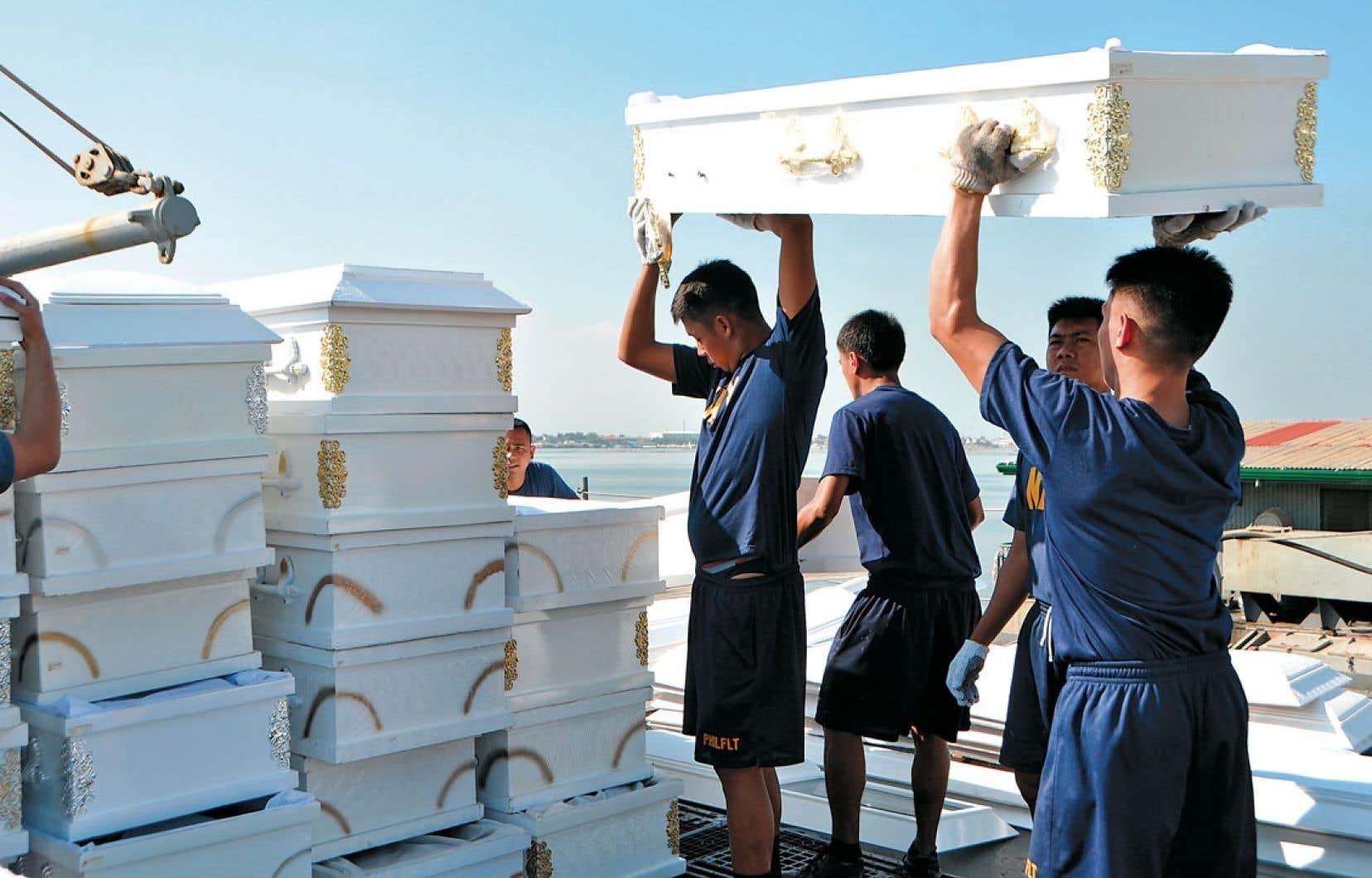<div> Cette photo datant du 11 décembre dernier et publiée par la marine philippine montre le chargement de cercueils offerts aux victimes du typhon Bopha.</div>