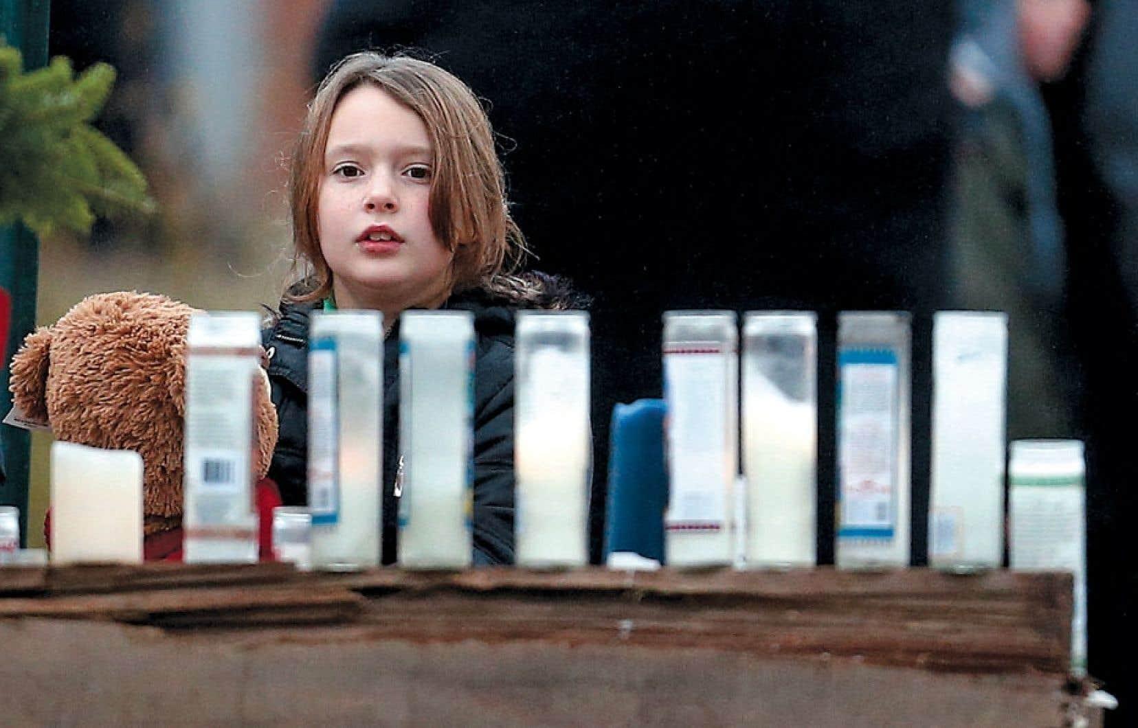 <div> Une jeune fille se recueillant devant un mémorial improvisé dressé au cœur de la ville de Newtown, au Connecticut.</div>