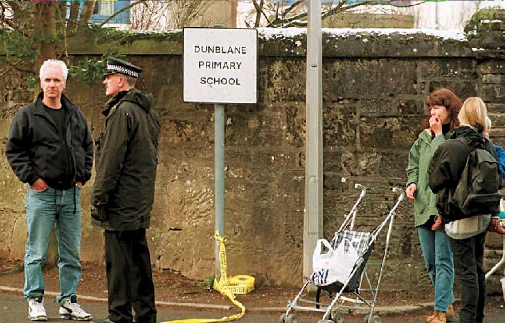 Un petit groupe de résidants de Dunblane, en Écosse, à l'entrée de l'école primaire où a eu lieu la tragédie qui a fait 15 morts en 1997.