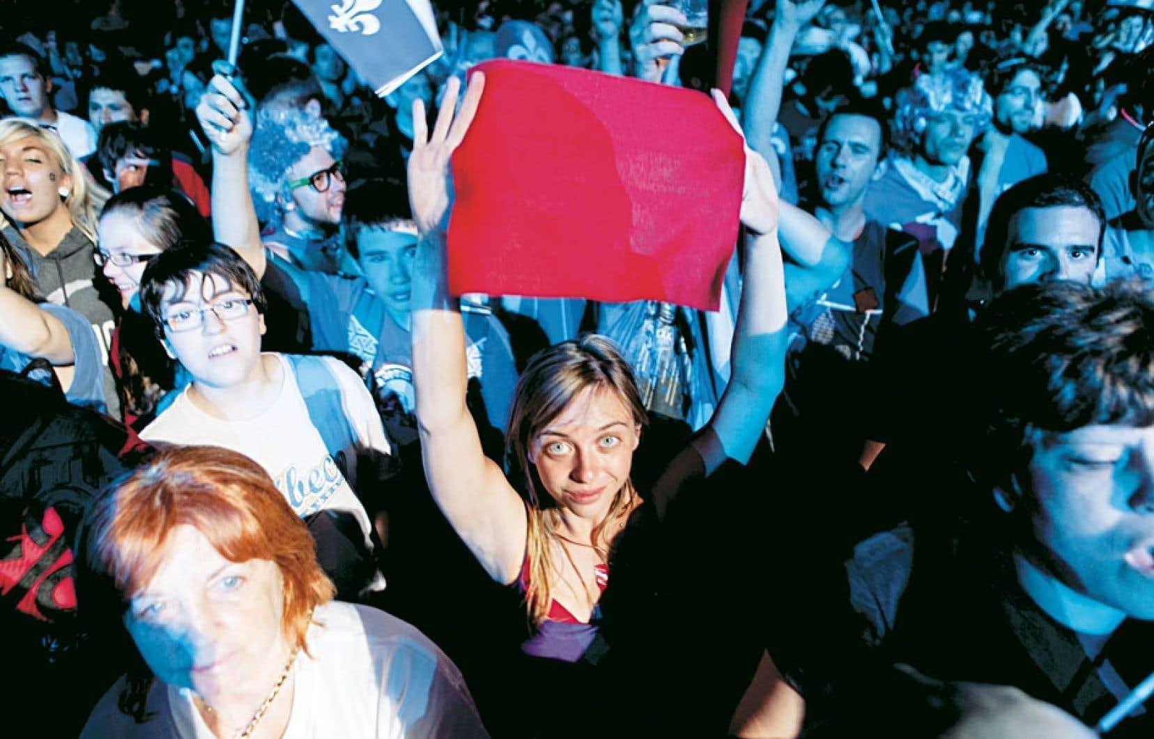 <div> Une jeune femme brandissant un carré rouge lors des célébrations de la fête nationale sur les plaines d'Abraham, le 24 juin dernier à Québec</div>