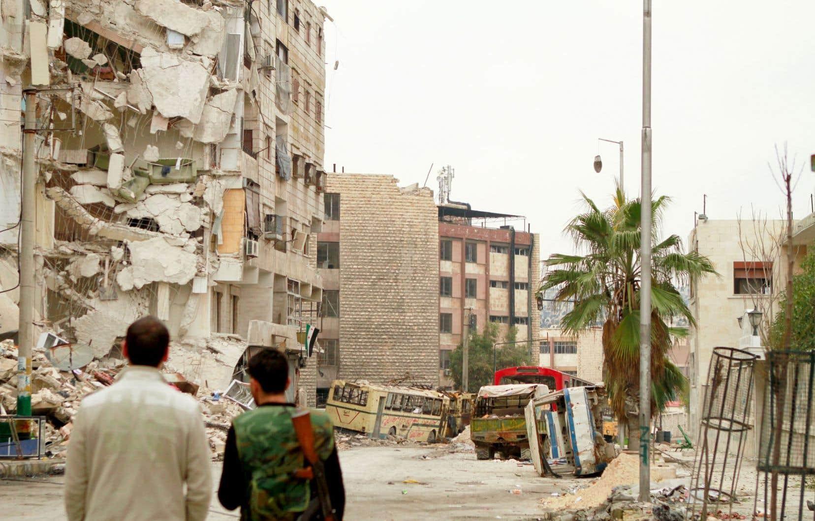 Des rebelles syriens constatent les dégâts dans une banlieue d'Alep.