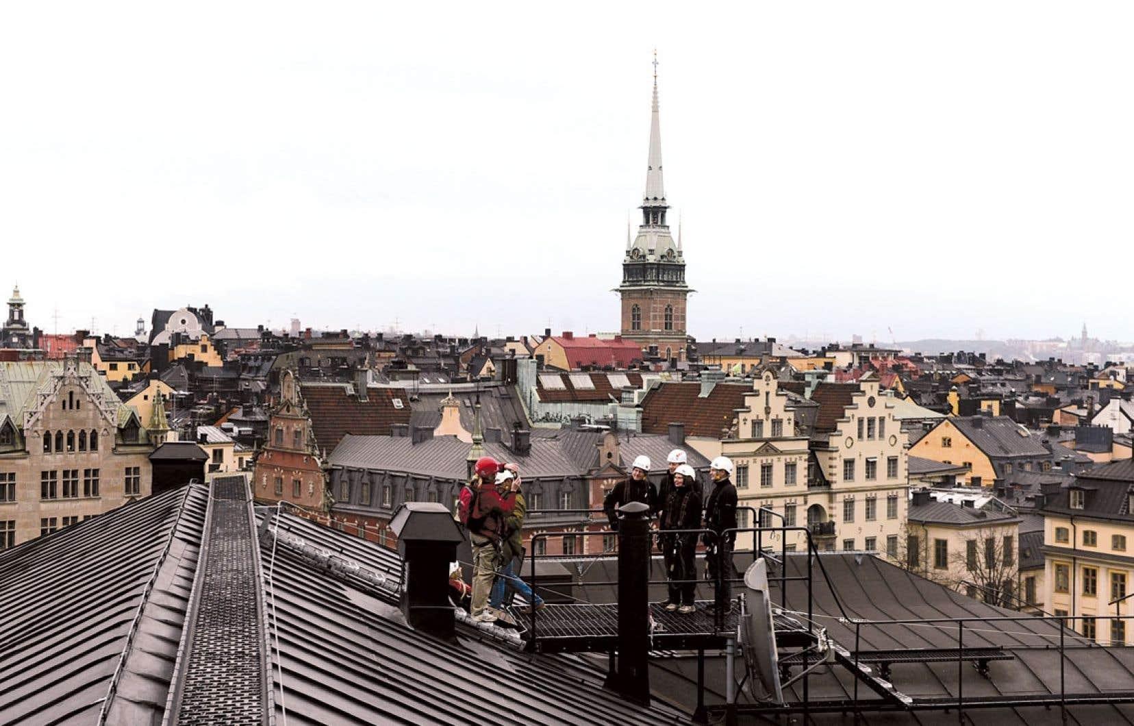 Des touristes écoutent leur guide lors d'une «tournée sur les toits» pour observer la vieille ville de Stockholm, en Suède, du haut d'un édifice dans l'îlot de Riddarholmen («l'îlot des chevaliers»).