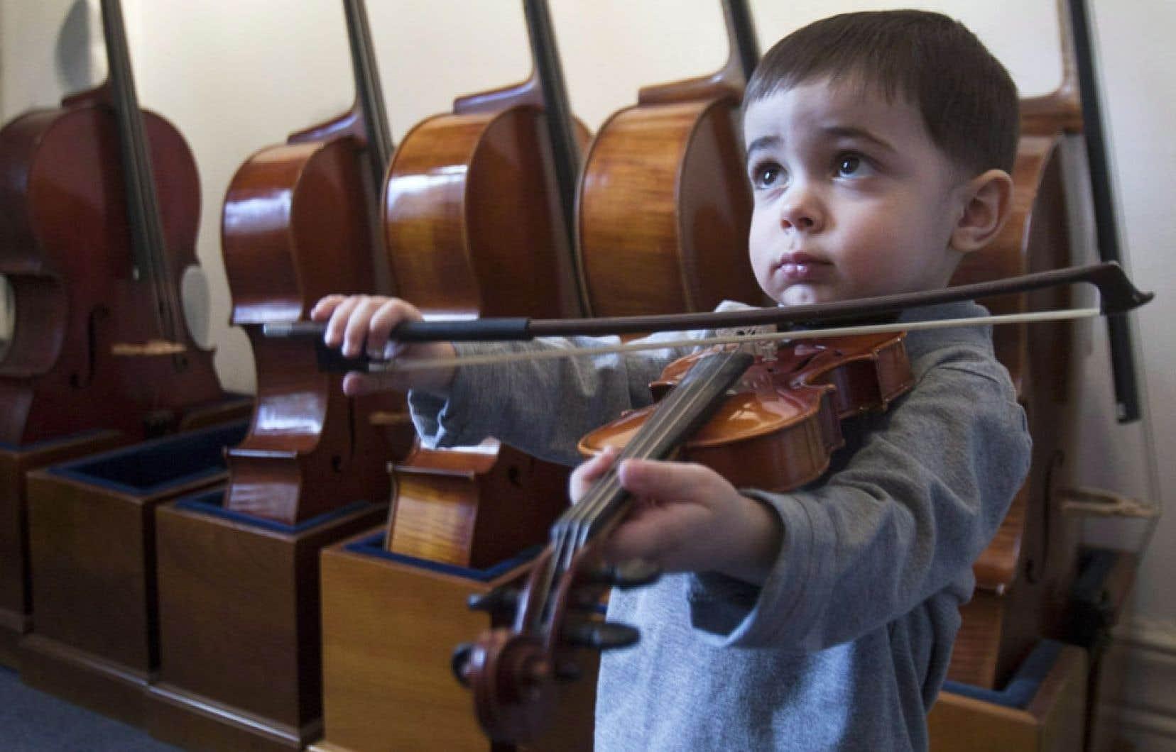 Un très jeune violoniste essaie un instrument dans la boutique d'un luthier montréalais. Si l'expérience musicale débute durant une période où la plasticité du cerveau est accrue, elle modifiera le cerveau, et permettra ainsi d'apprendre plus vite, estiment des chercheurs.