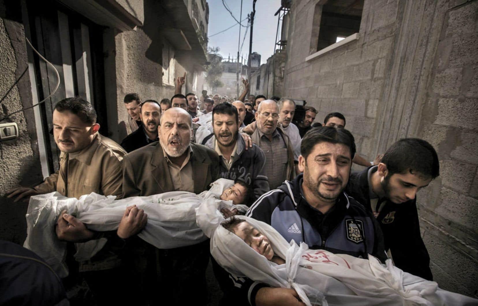 <div> Photographie ayant remporté le World Press 2012, représentant des hommes transportant les cadavres de deux enfants à Gaza.</div>