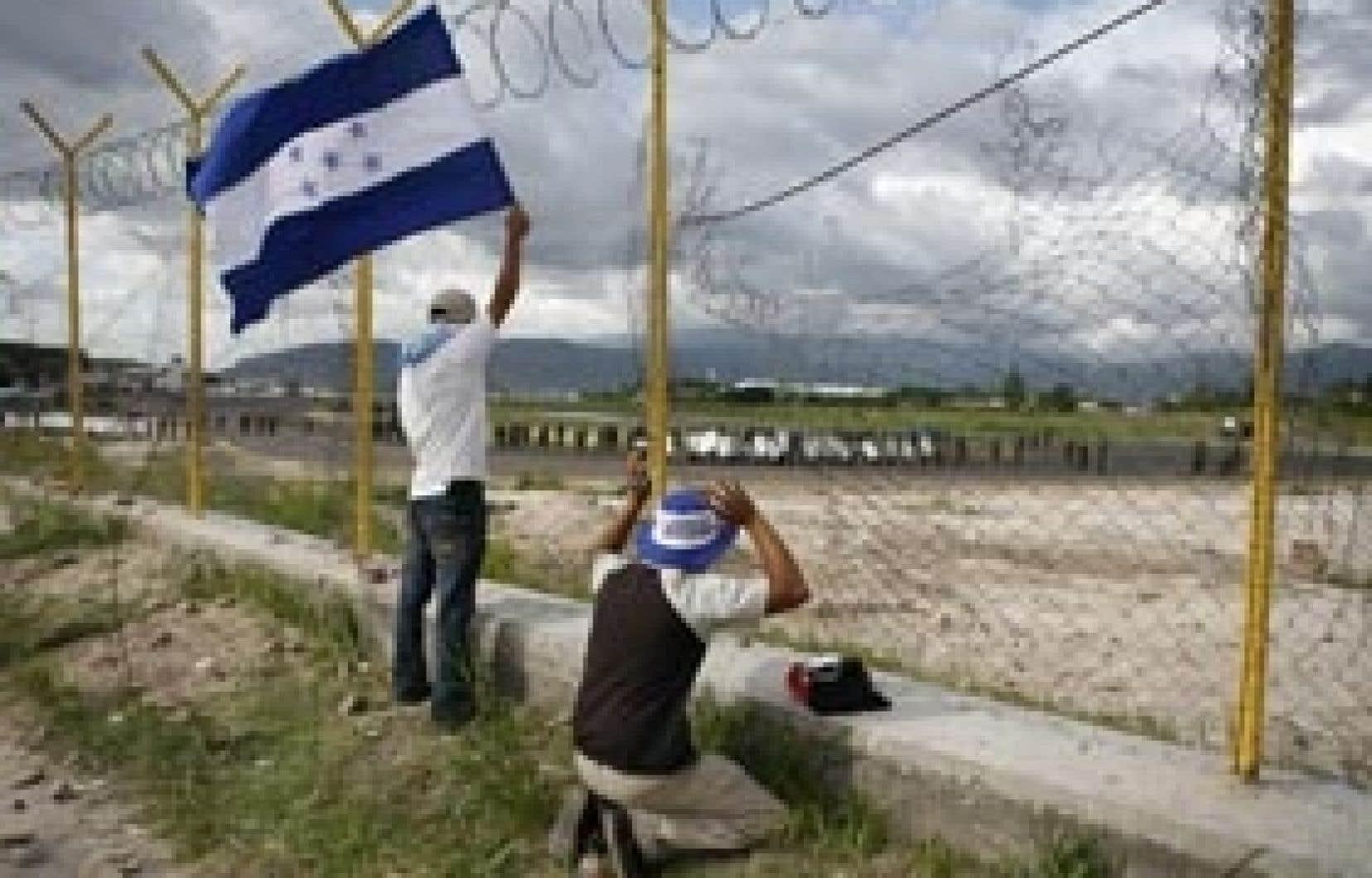 Des partisans du président déchu, Manuel Zelaya, observent les militaires qui occupent la piste de l'aéroport de la capitale.