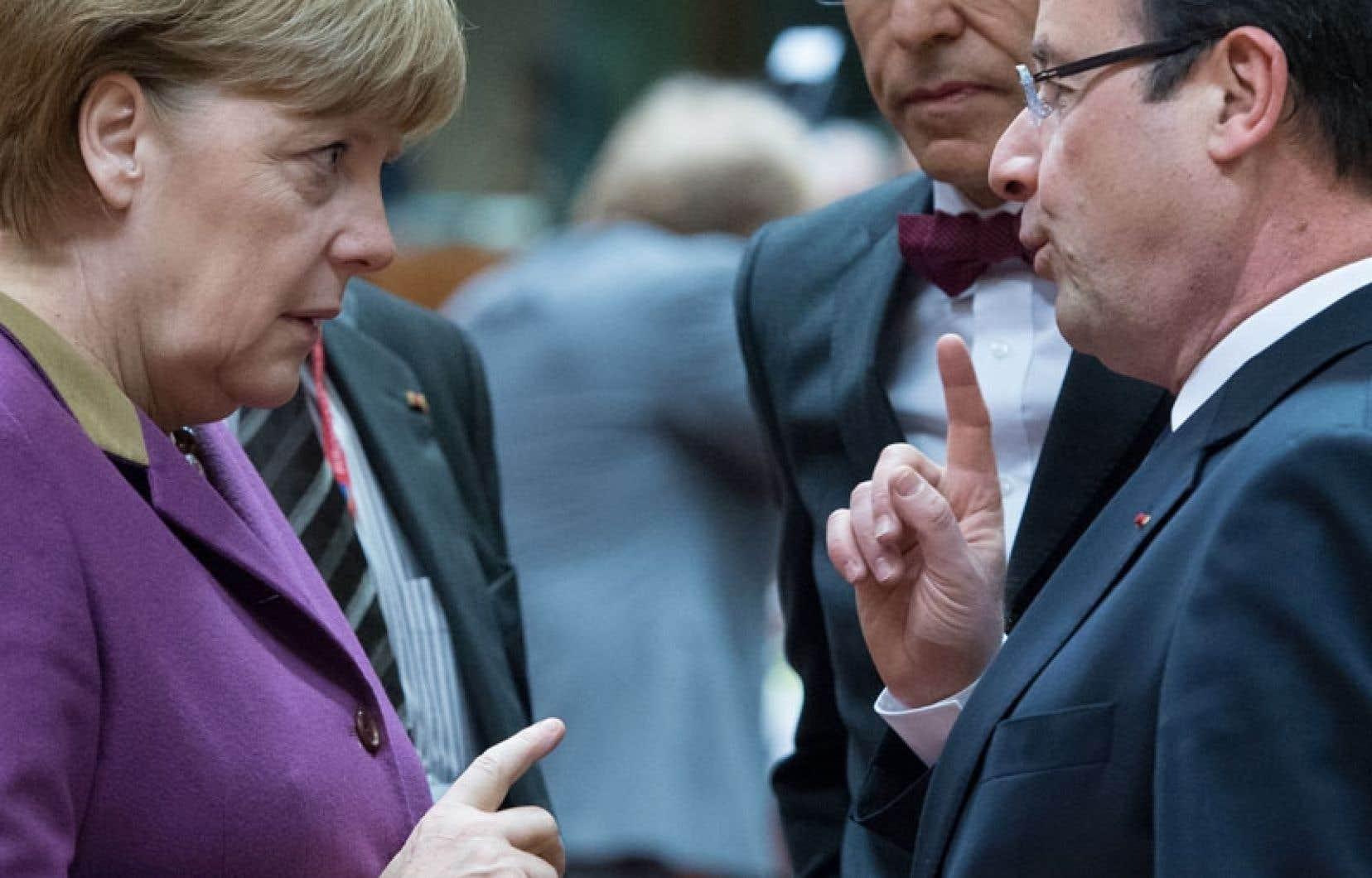 La chancelière allemande, Angela Merkel, et le président français, François Hollande, discutant du cas de Chypre.