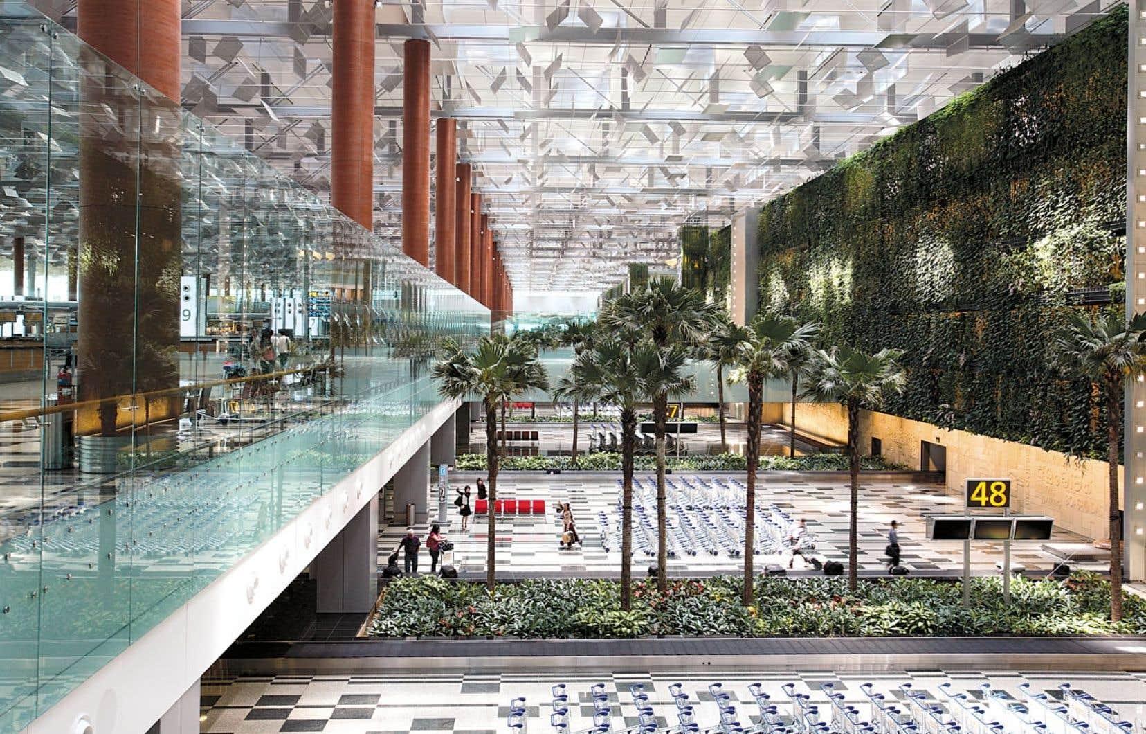 Un immense mur vert surplombe l'aire de récupération des bagages au terminal 3 de Changi.