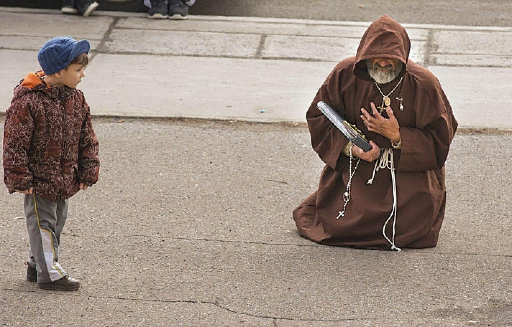 Des centaines de croyants ont pris part à la 41e édition de la Marche du pardon à Montréal ce Vendredi saint. Au coin des rues Jarry et Henri-Julien, arrêté à l'une des stations représentant le Chemin de croix du Christ, ce petit garçon observe un laïc non voyant ayant fait la procession pieds nus.