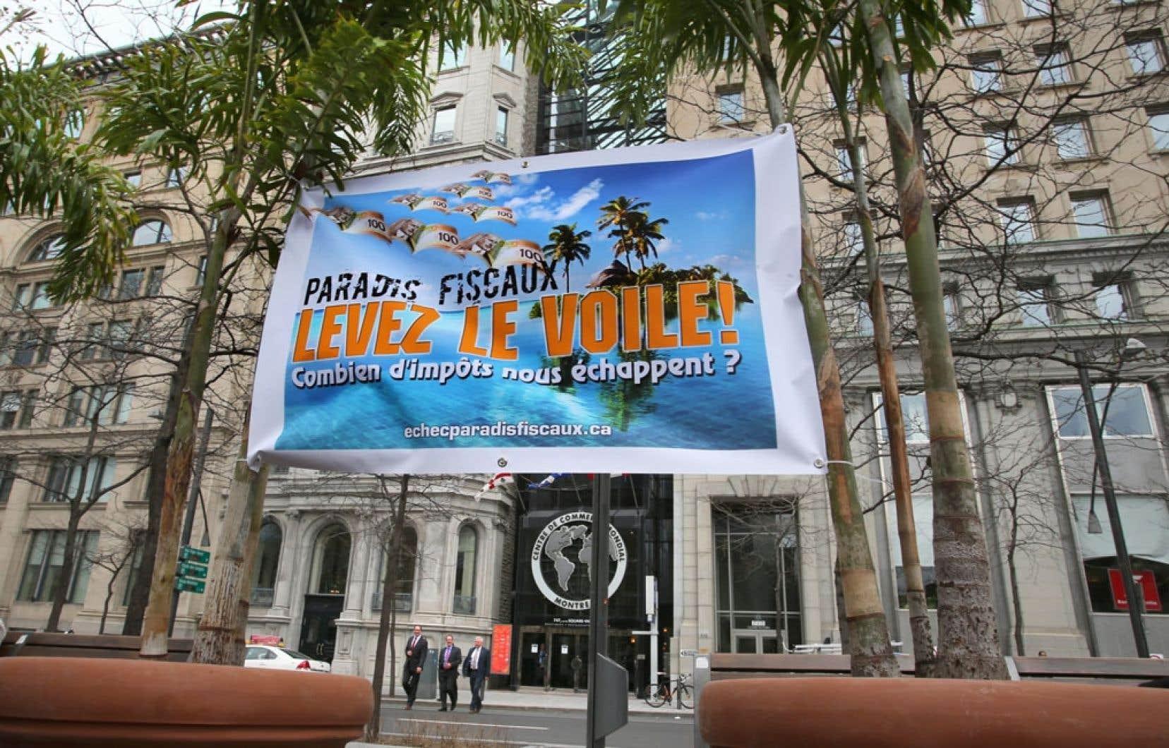 La coalition Échec aux paradis fiscaux avait installé des palmiers et une grande affiche devant le Centre du commerce mondial, à Montréal, où le ministre québécois des Finances, Nicolas Marceau, a ses bureaux, à l'occasion du lancement de sa campagne « Levez le voile ! ».