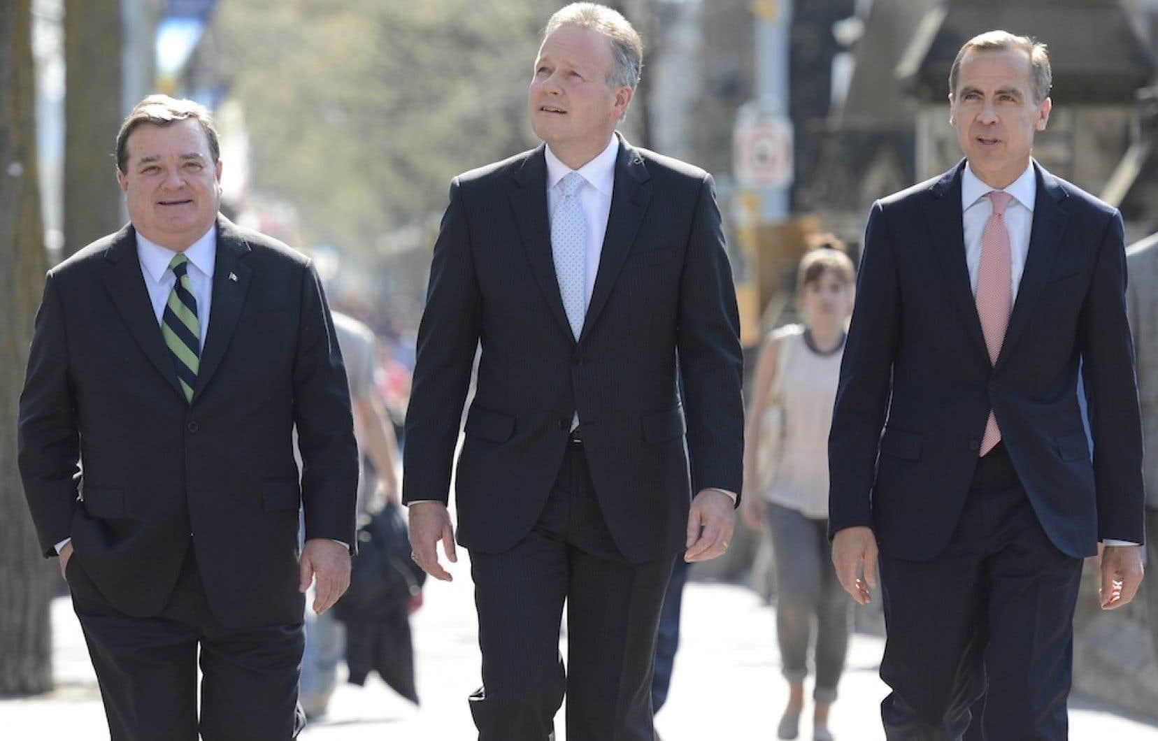 Le ministre des Finances, Jim Flaherty, et le gouverneur sortant, Mark Carney, entourent le prochain patron de la Banque du Canada, Stephen Poloz.