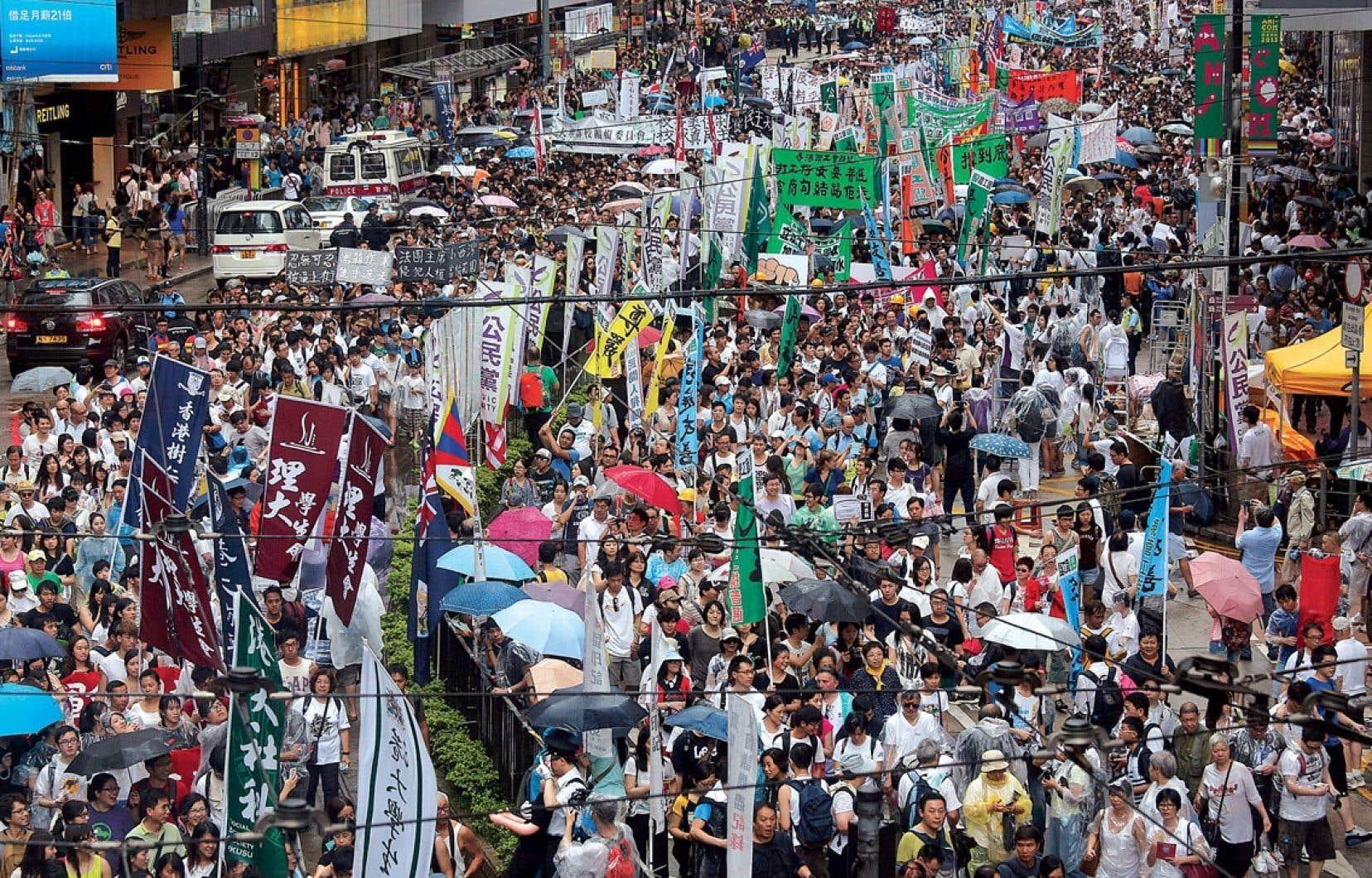 Des dizaines de milliers de personnes ont manifesté dans les rues de Hong Kong, lundi, afin d'exiger le départ de leur dirigeant pro-Pékin et de réclamer la mise en place de réformes démocratiques.