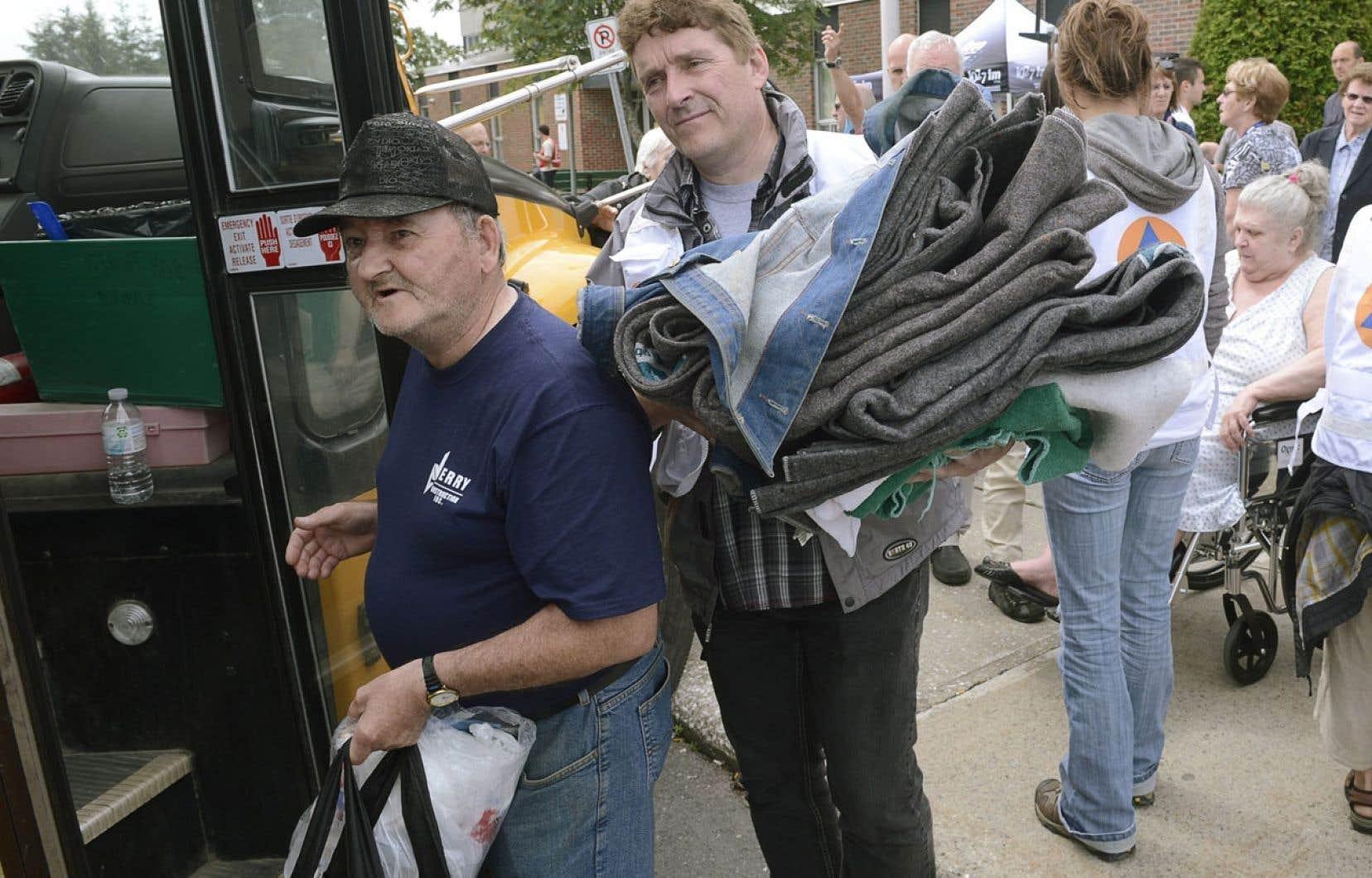 Un bénévole aide un résidant de Lac-Mégantic à transporter des effets personnels à bord d'un autobus d'écoliers. Plusieurs évacués ont pu rentrer chez eux lundi.