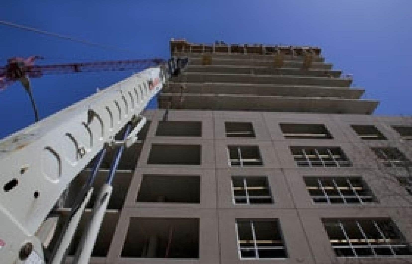 Un immeuble en construction à Montréal. Très sensibles aux taux d'intérêt, les secteurs immobilier et de l'automobile affichent toujours une belle vigueur au pays.