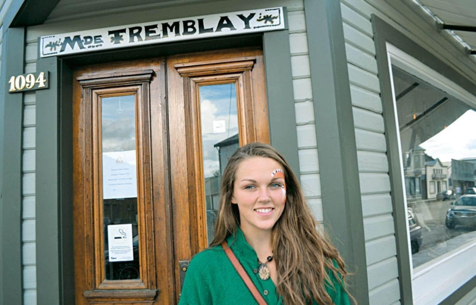 La jeune Franco-Yukonnaise Maya Poirier photographiée devant un magasin de Dawson City portant le nom d'une pionnière du Yukon, Émilie Tremblay, qui a aussi laissé son nom à l'école francophone de Whitehorse.