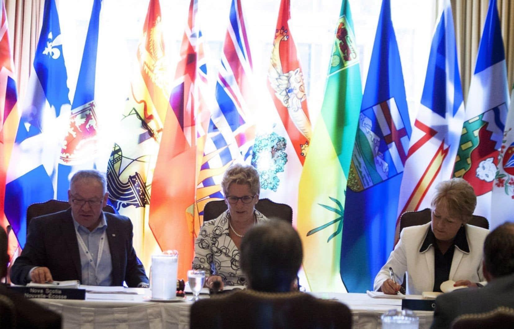 La première ministre ontarienne, Kathleen Wynne (au centre), entourée de ses homologues Darrell Dexter, de la Nouvelle-Écosse, et Pauline Marois, du Québec, lors d'une séance de travail jeudi.