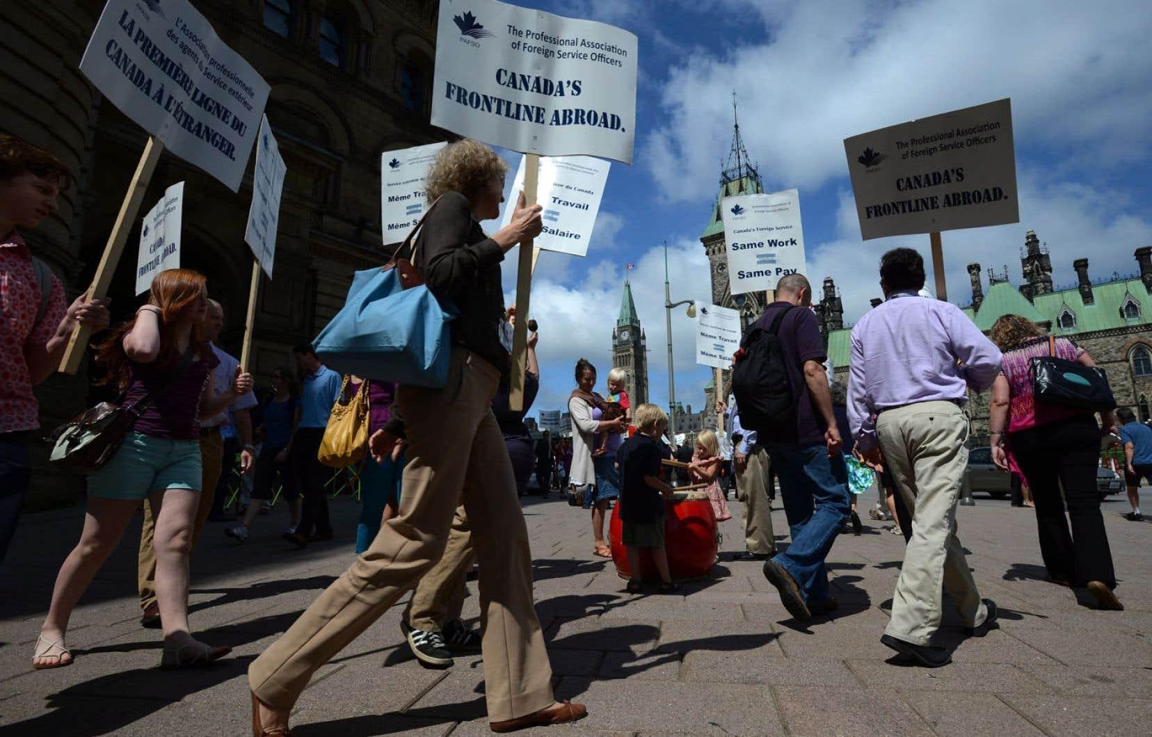 Pancartes à la main pour exprimer leur mécontentement, plus de 200 agents du service extérieur ont manifesté mardi devant les bureaux du premier ministre Stephen Harper, à Ottawa.
