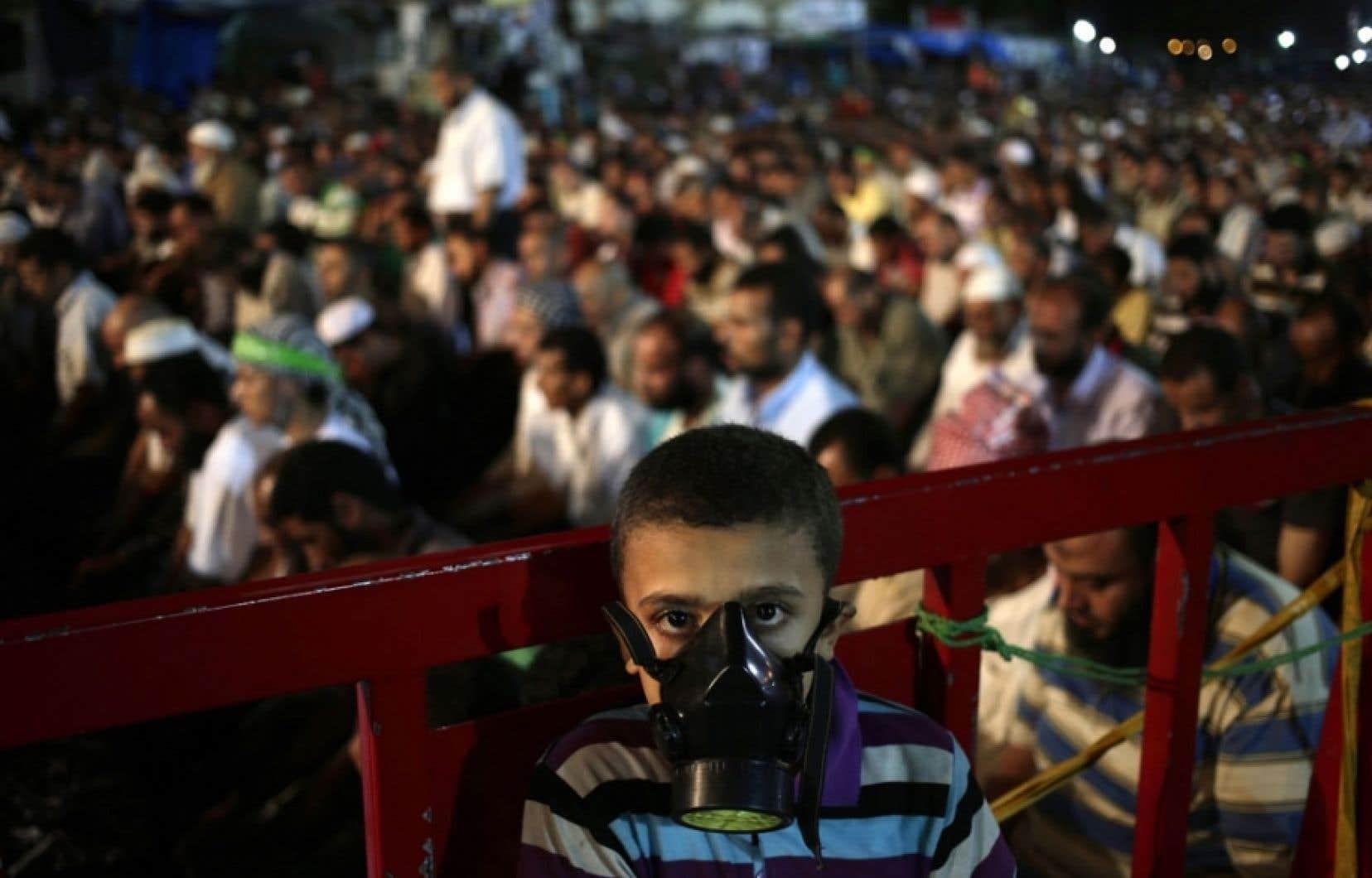 Un garçon porte un masque à gaz devant des partisans du président déchu Mohammed Morsi. Des manifestants ont installé un camp et organisent des rassemblements quotidiens, au Caire.