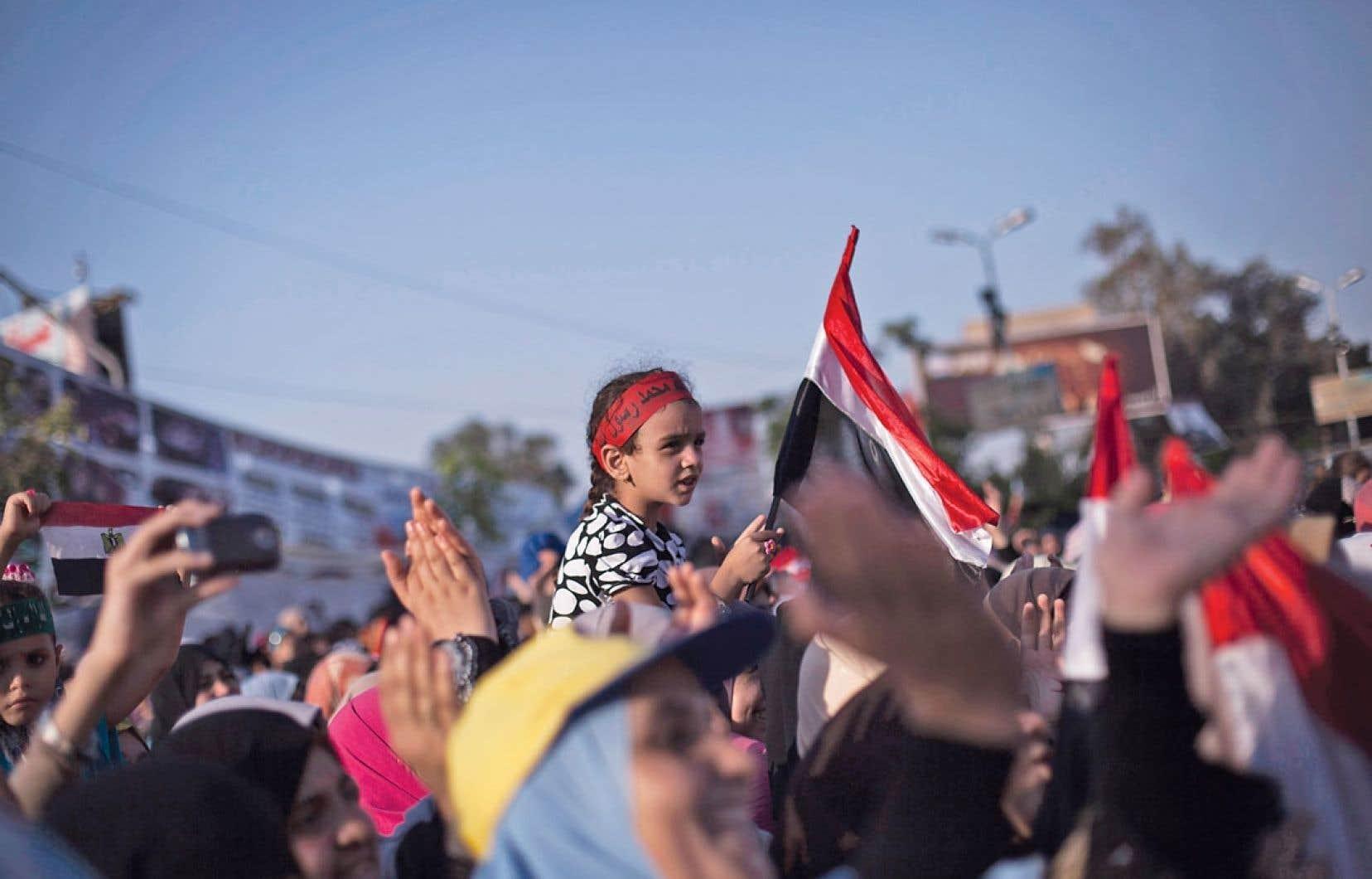 Une petite fille égyptienne agitait un drapeau entourée par des partisans de Morsi criant des slogans contre l'armée sur la place Rabaa al-Adawiya du Caire, dimanche.