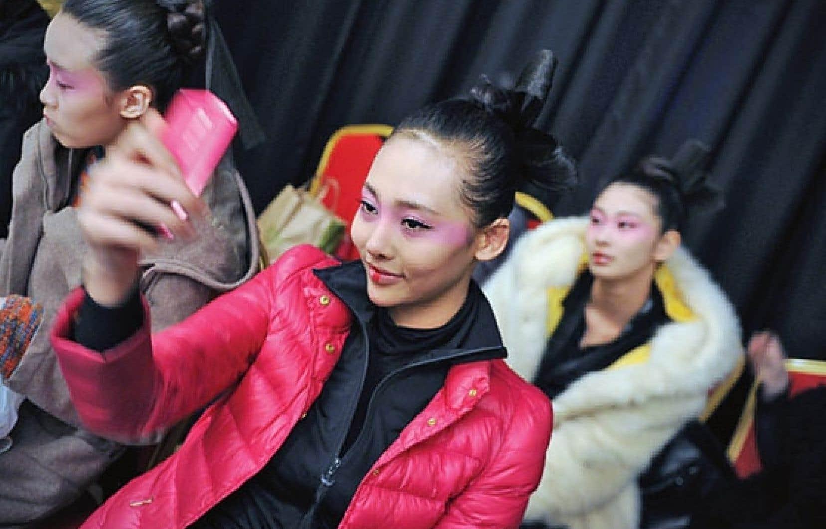 Une jeune femme se prend en photo à l'aide de son cellulaire lors d'un défilé à Pékin, en Chine.