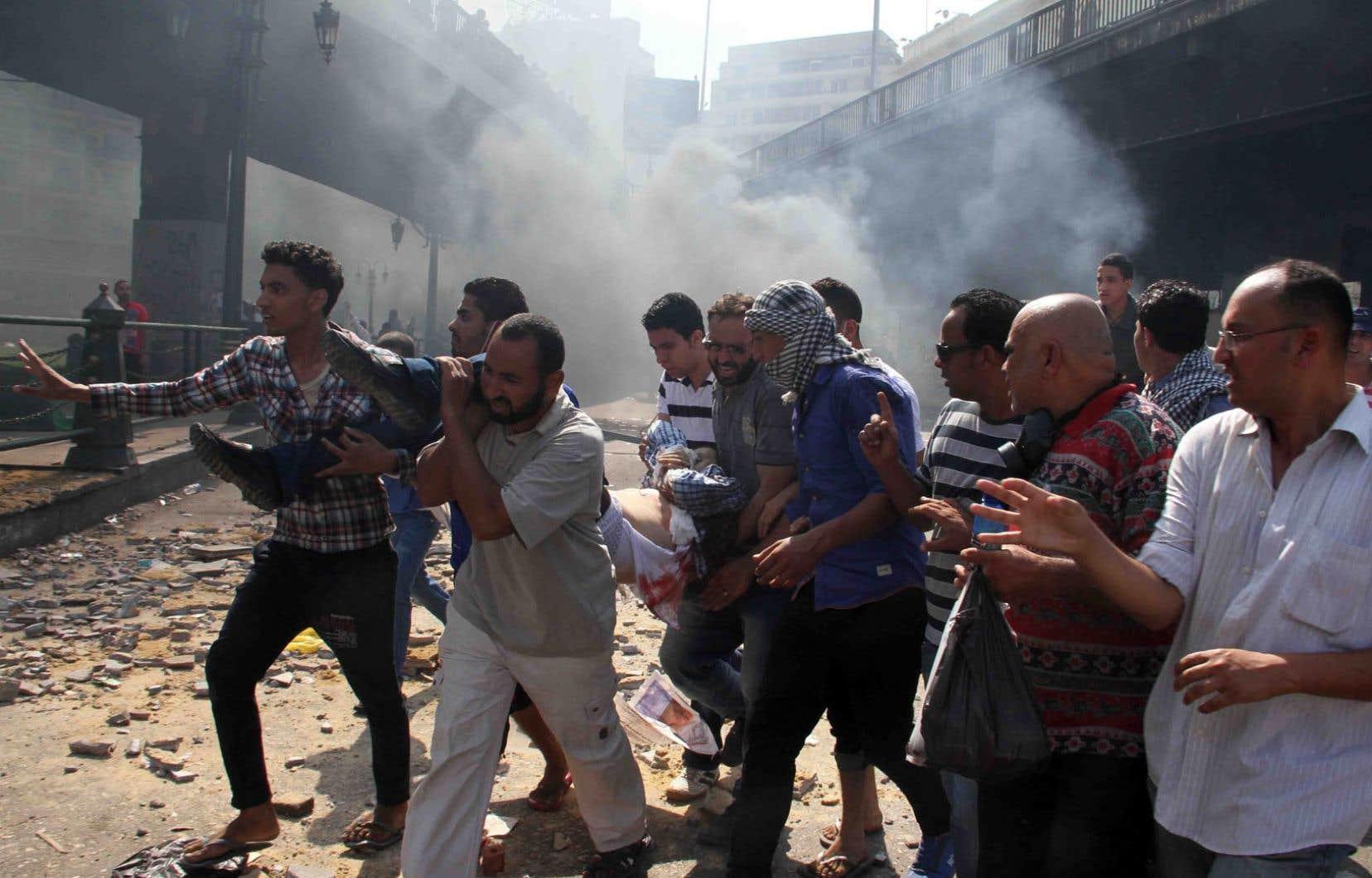 Des sympathisants des Frères musulmans transportent un des leurs blessé vendredi lors d'un affrontement avec les policiers, place Ramsès, au Caire.