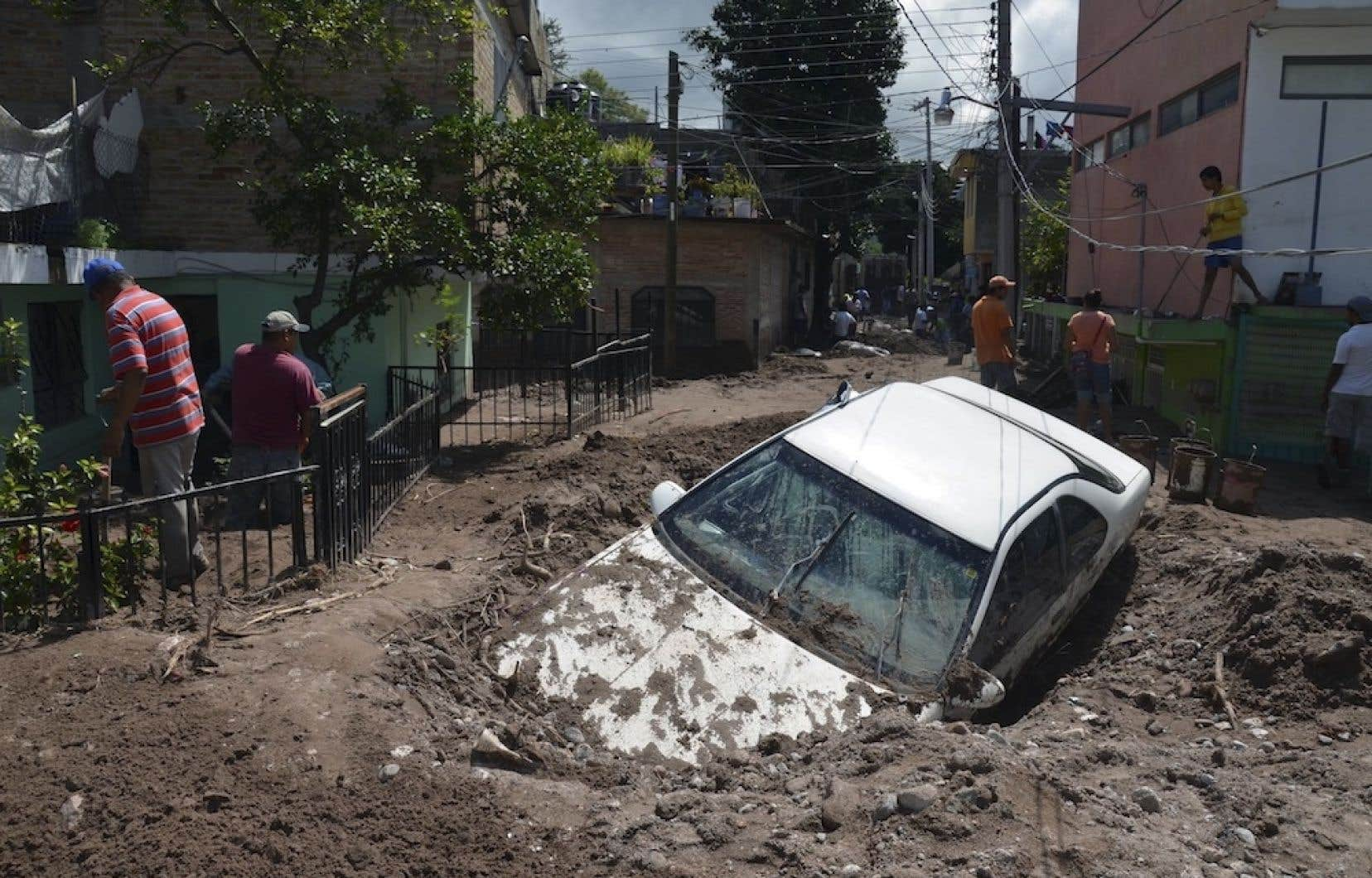 Une voiture est enterrée dans la boue, à Mexico, après le passage de la tempête tropicale Manuel.