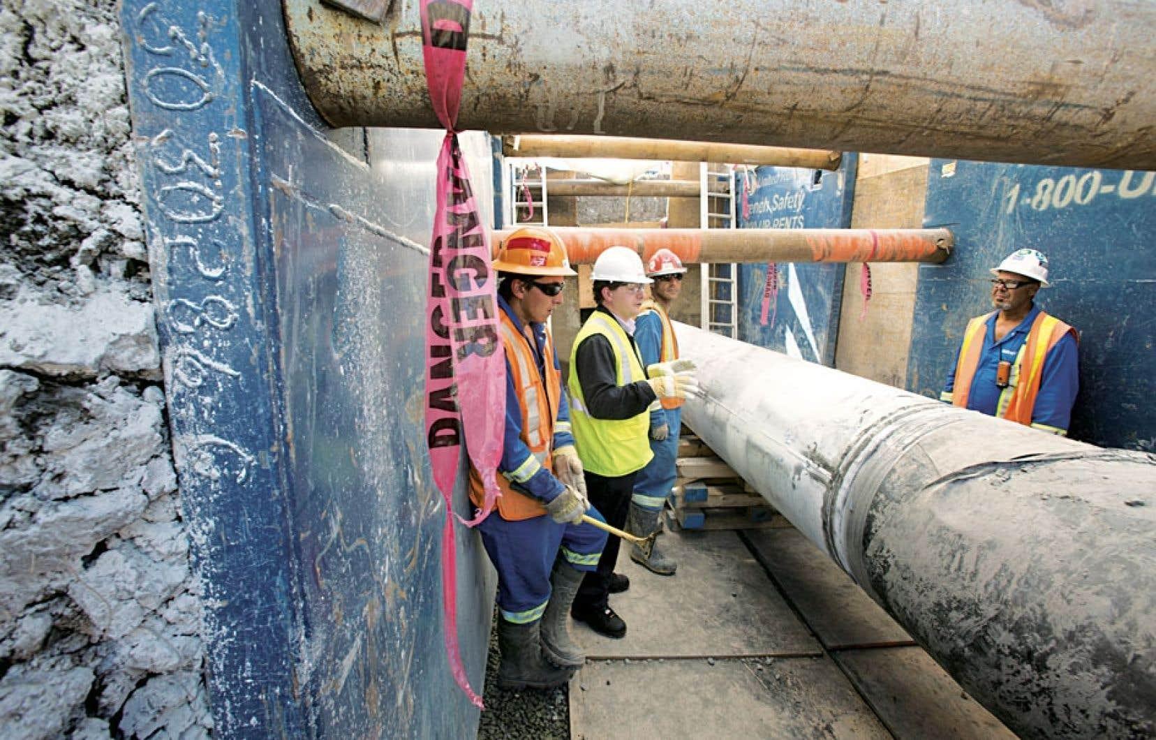 Des travailleurs mandatés par Enbridge examinent un tronçon de la ligne 9B le long de l'autoroute 15 afin de constater de visu si des dommages doivent être réparés.