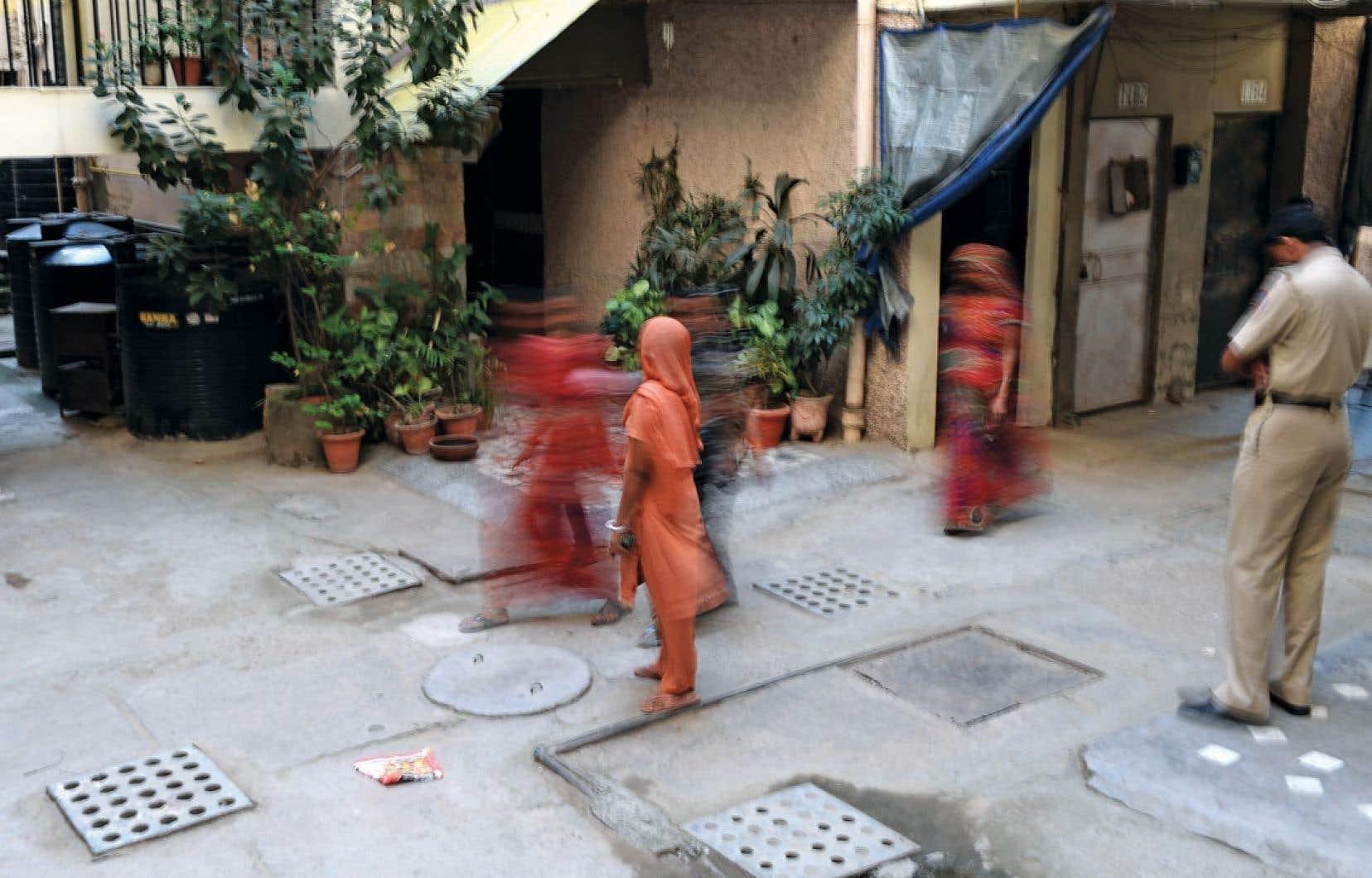 Des piétons passant devant un appartement où une jeune femme de ménage aurait été torturée, à Vasant Kunj, en octobre dernier.